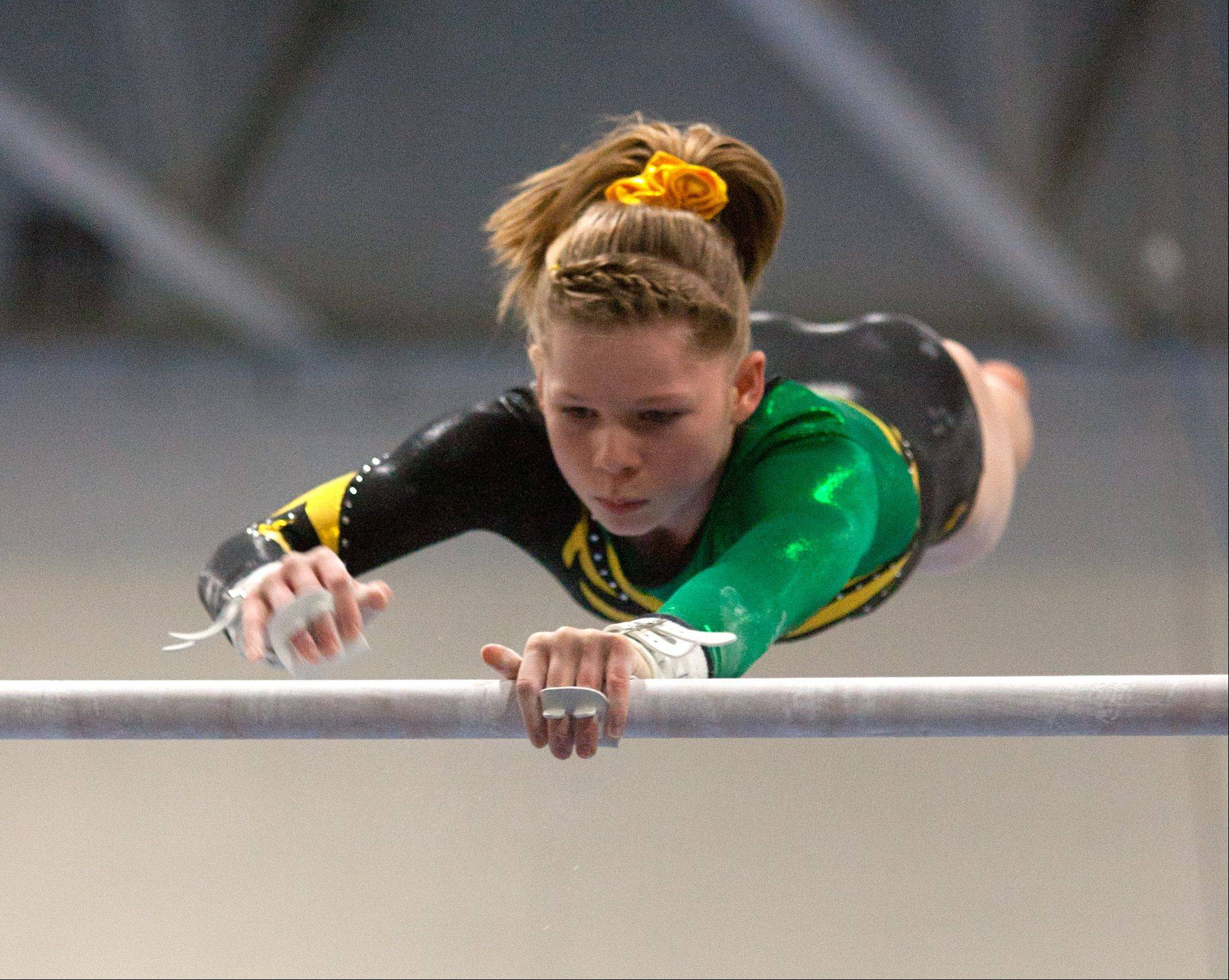 Waubonsie Valley High School's Alaina Kapla performs her uneven parallel bar during the York Girls' Gymnastics Invite.