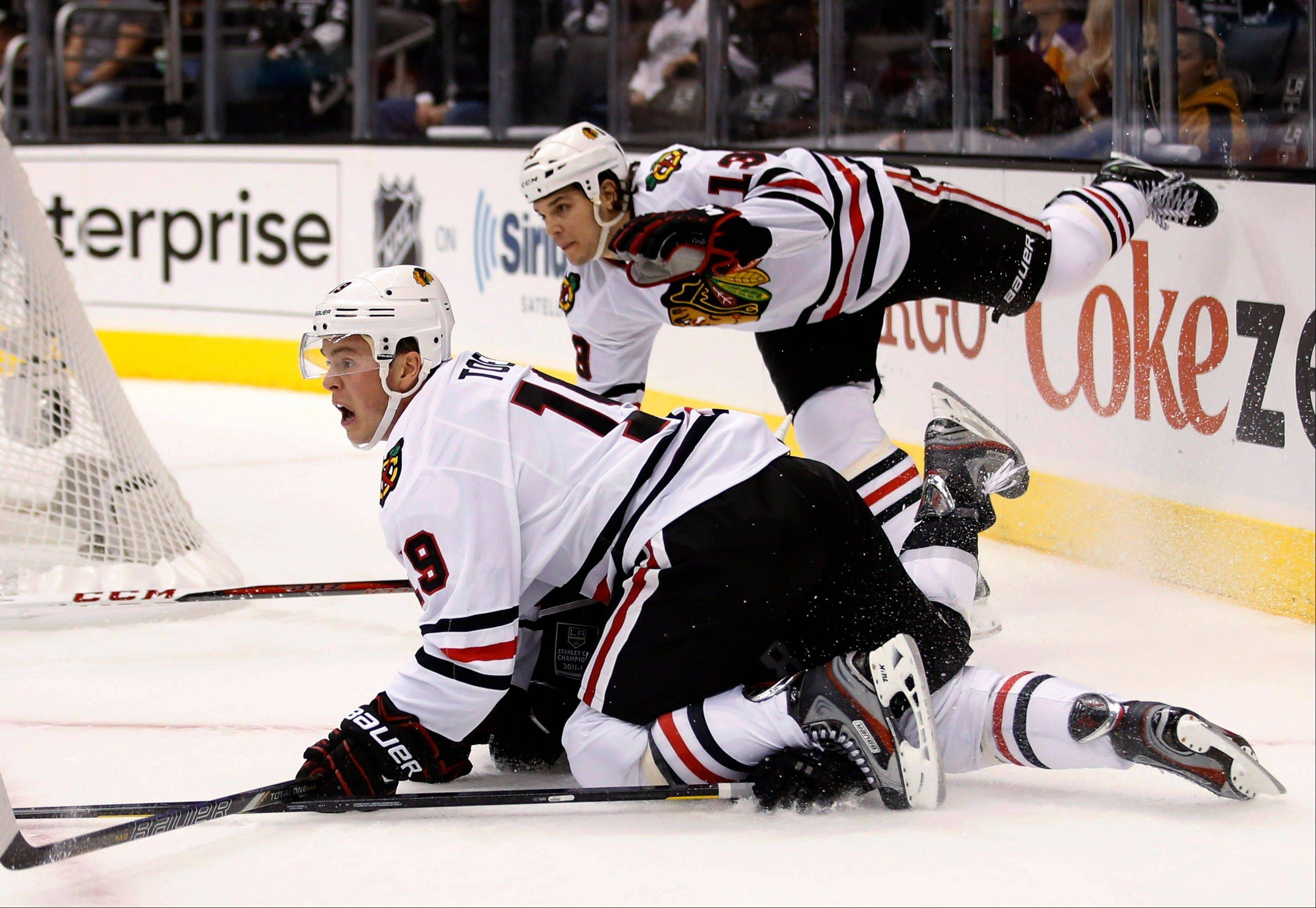 Los Angeles Kings' Drew Doughty is pinned by Chicago Blackhawks' Jonathan Toews (19) during the first period in Los Angeles. The Blackhawks' Daniel Carcillo is at rear.