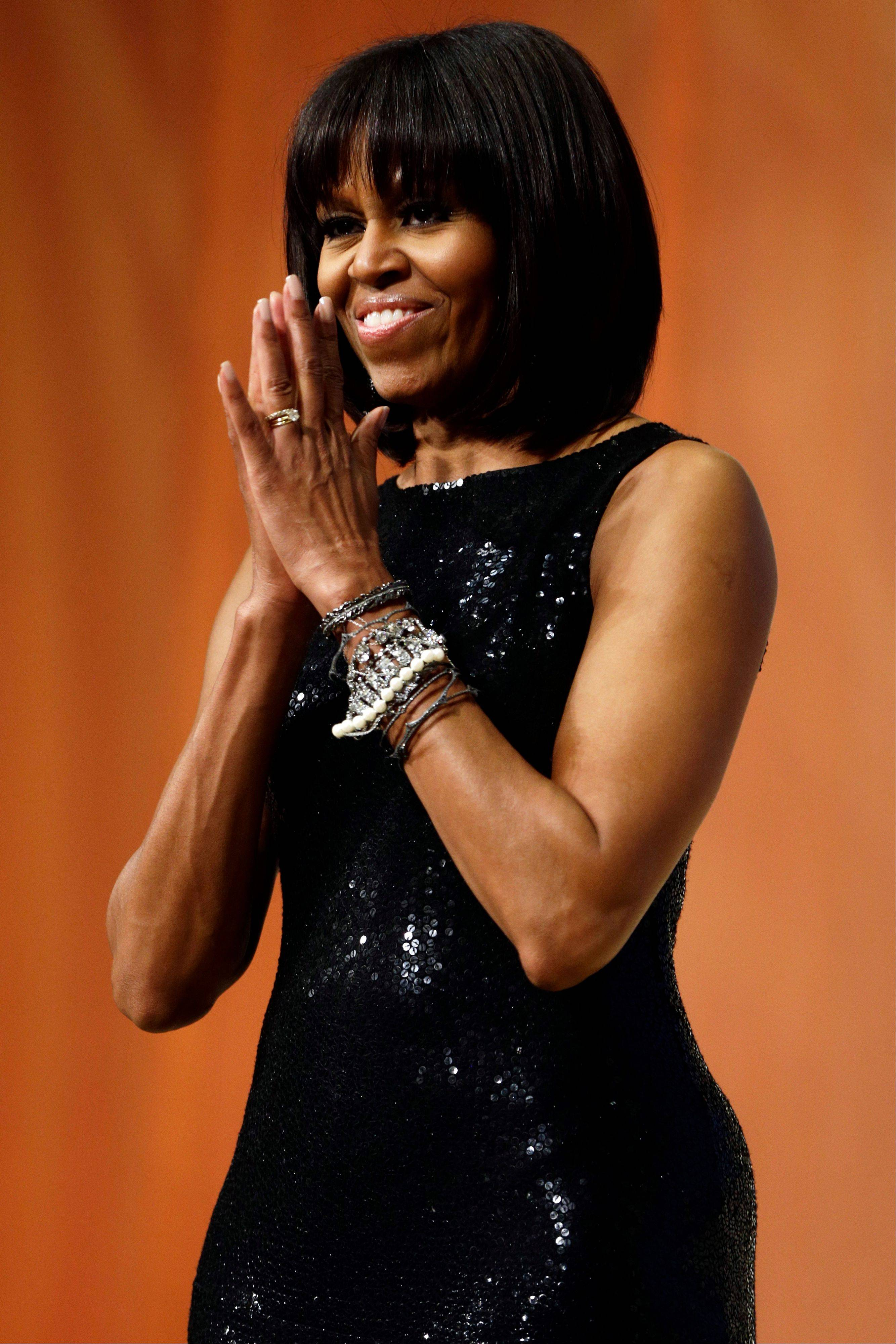ASSOCIATED PRESS First lady Michelle Obama acknowledges the crowd as President Obama speaks to supporters and donors at an inaugural reception for the 57th Presidential Inauguration at The National Building Museum in Washington on Sunday.