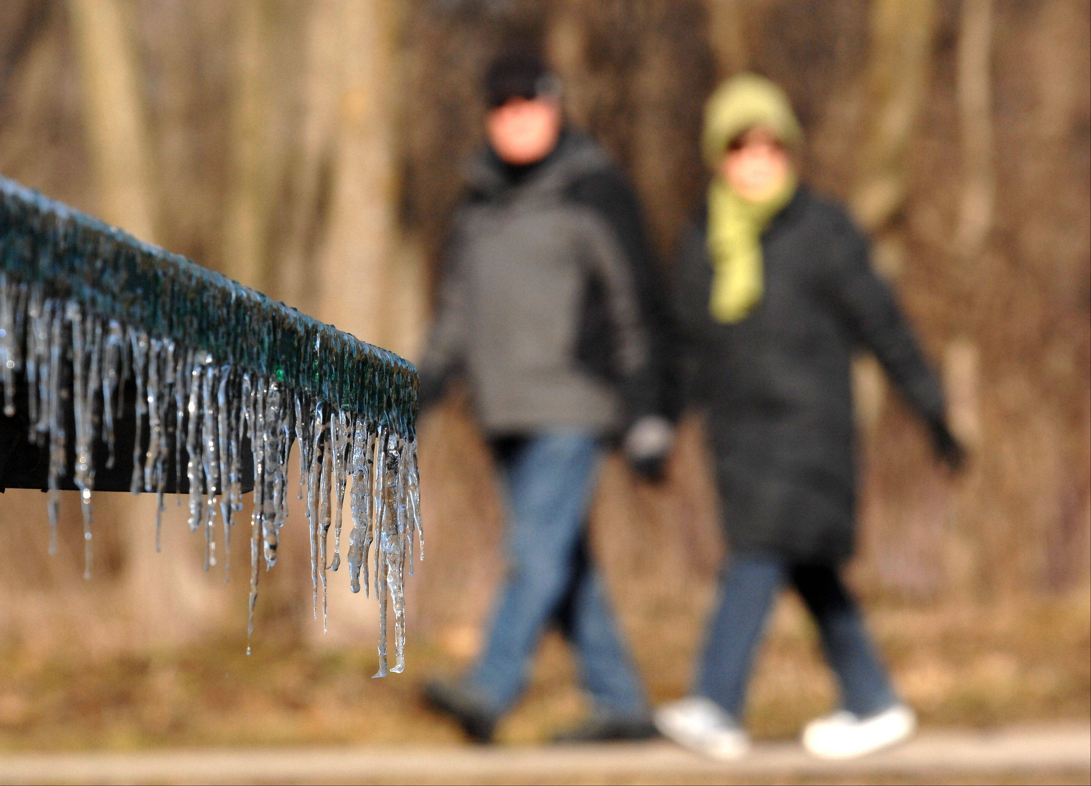 Icicles hang from a picnic table as Sue and Les Dixon, of Geneva, brave temperatures in the teens for a walk near Fabyan Forest Preserve in Geneva Monday. They said they walk in the preserve a few days a week.