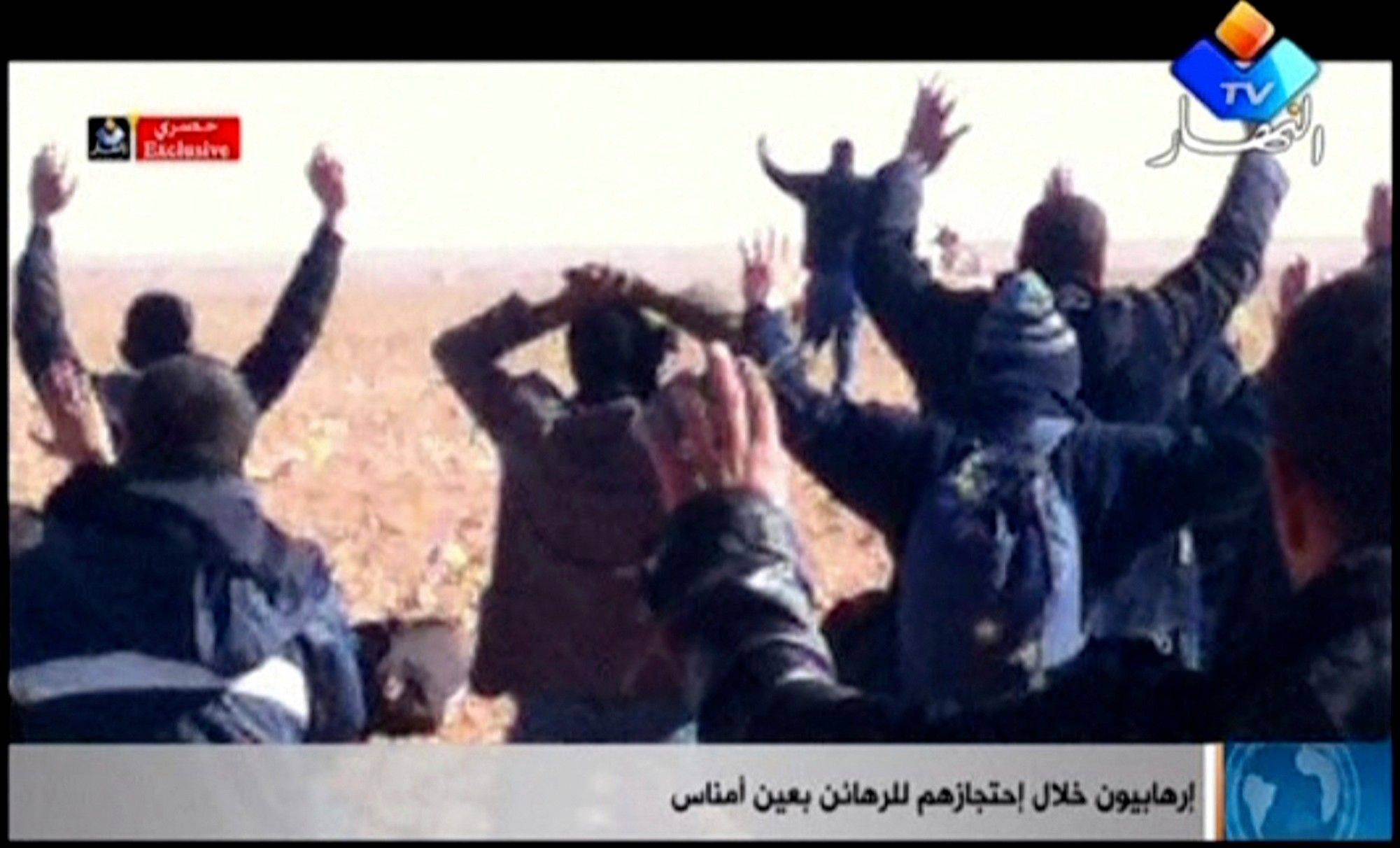 "In this image made from video, a group of people believed to be hostages kneel in the sand with their hands in the air at an unknown location in Algeria. An Algerian security official says de-mining squads searching for explosives found ""numerous"" bodies Sunday at a gas refinery where Islamic militants took dozens of foreign workers hostage."