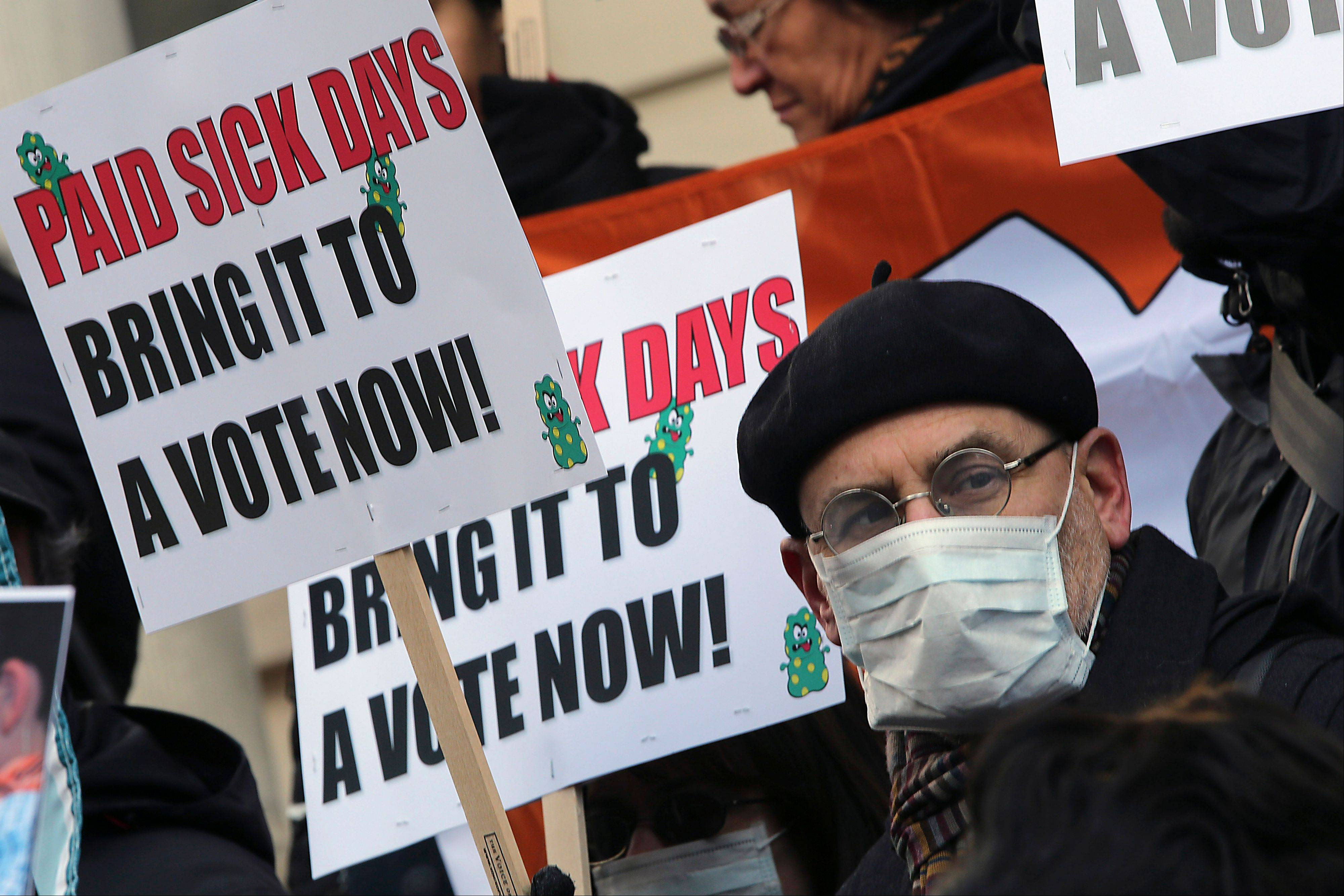 Activists hold signs during a rally at New York's City Hall on Friday to call for immediate action on paid sick days legislation in light of the continued spread of the flu.