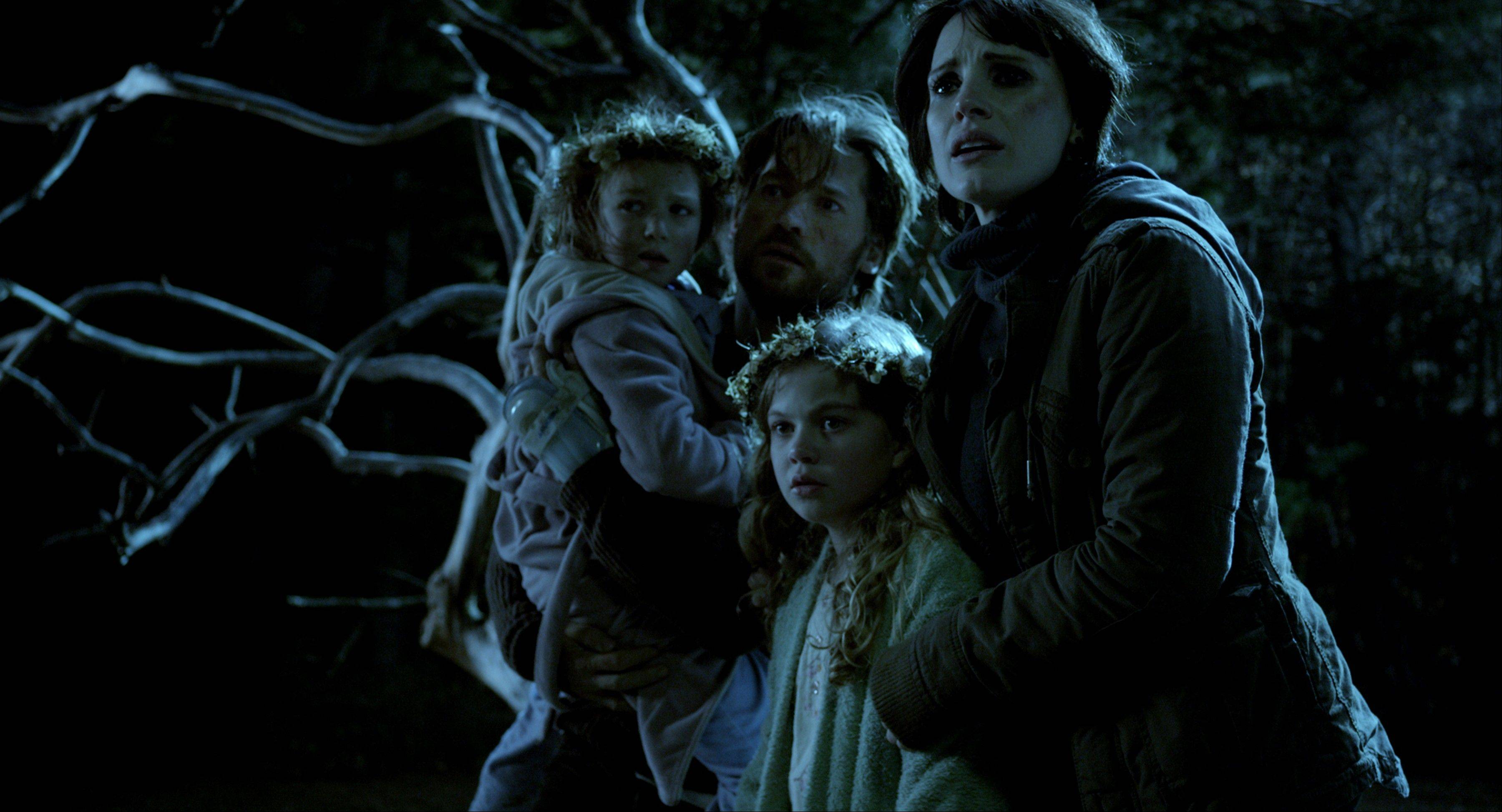 "This film image released by Universal Pictures shows, from left, Isabelle N�lisse, Nikolaj Coster-Waldau, Megan Charpentier and Jessica Chastain in a scene from ""Mama."" The horror flick landed the top spot at the box office with nearly $30 million."