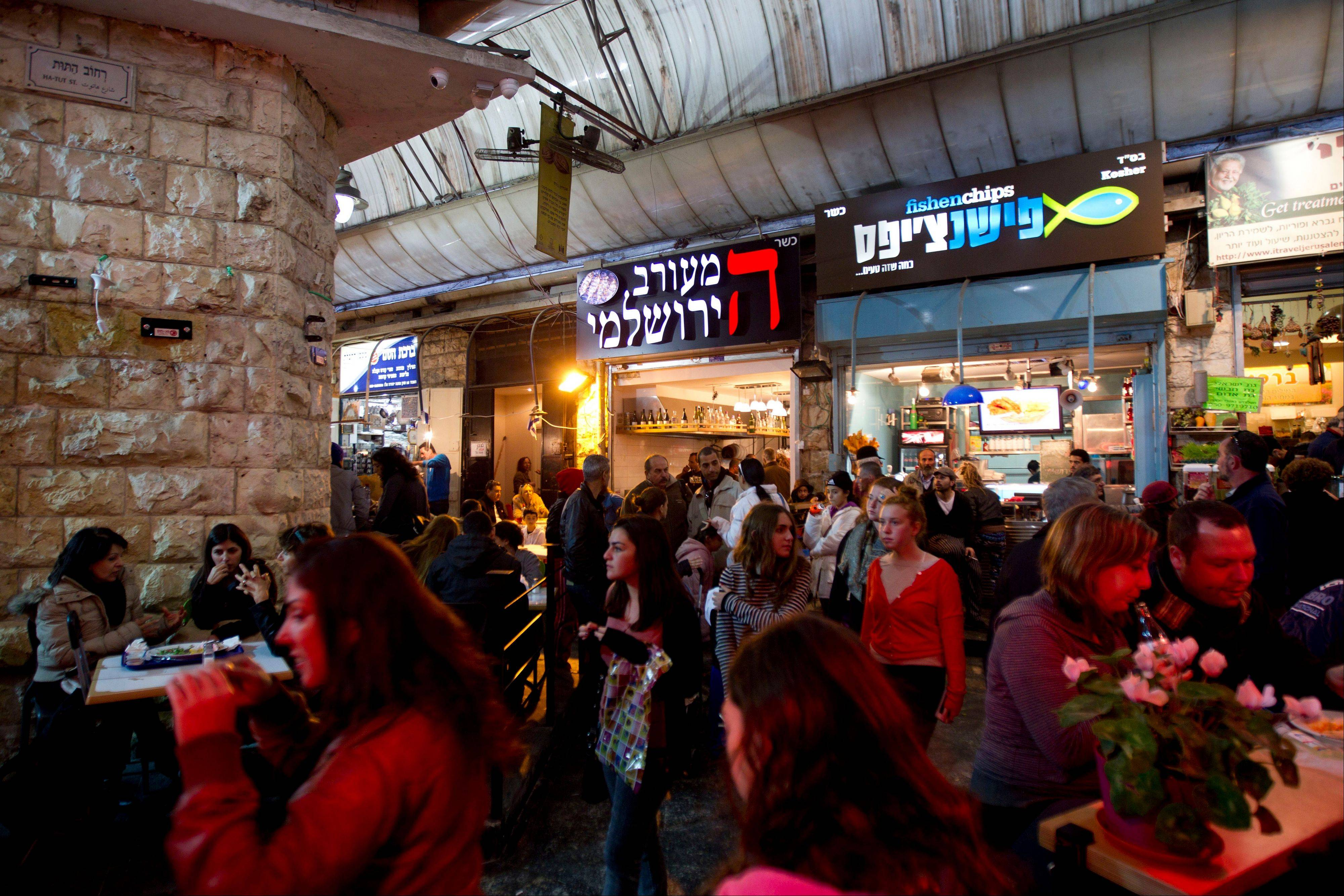 Visitors browse through the Mahane Yehuda Market, one of Jerusalem's free tourist attractions.