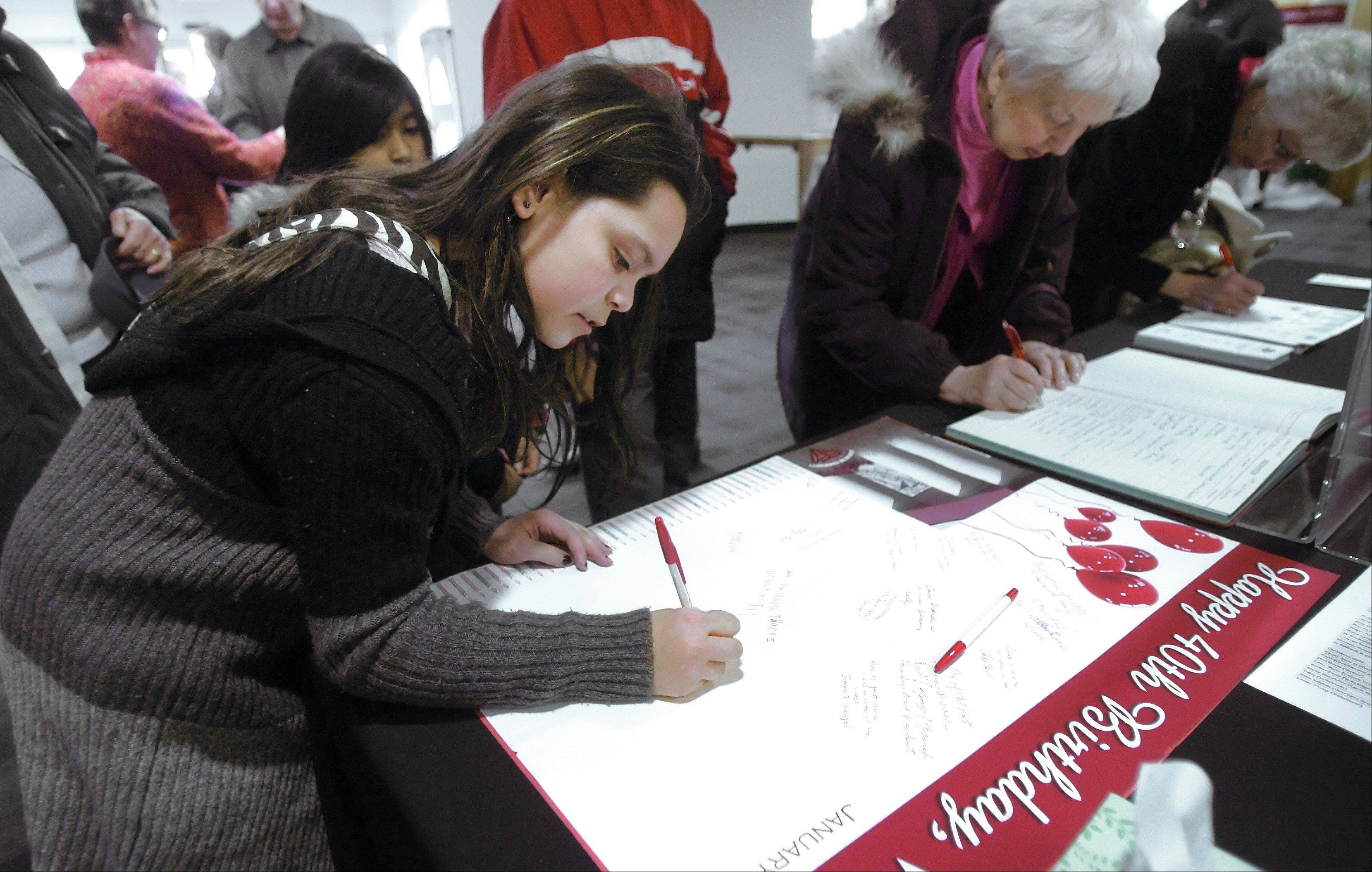Angelina Macias, 11, of Park City, signs a card during the Warren-Newport Public Library's 40th anniversary celebration Sunday in Gurnee. The special event featured food, games and actives focused on the anniversary.