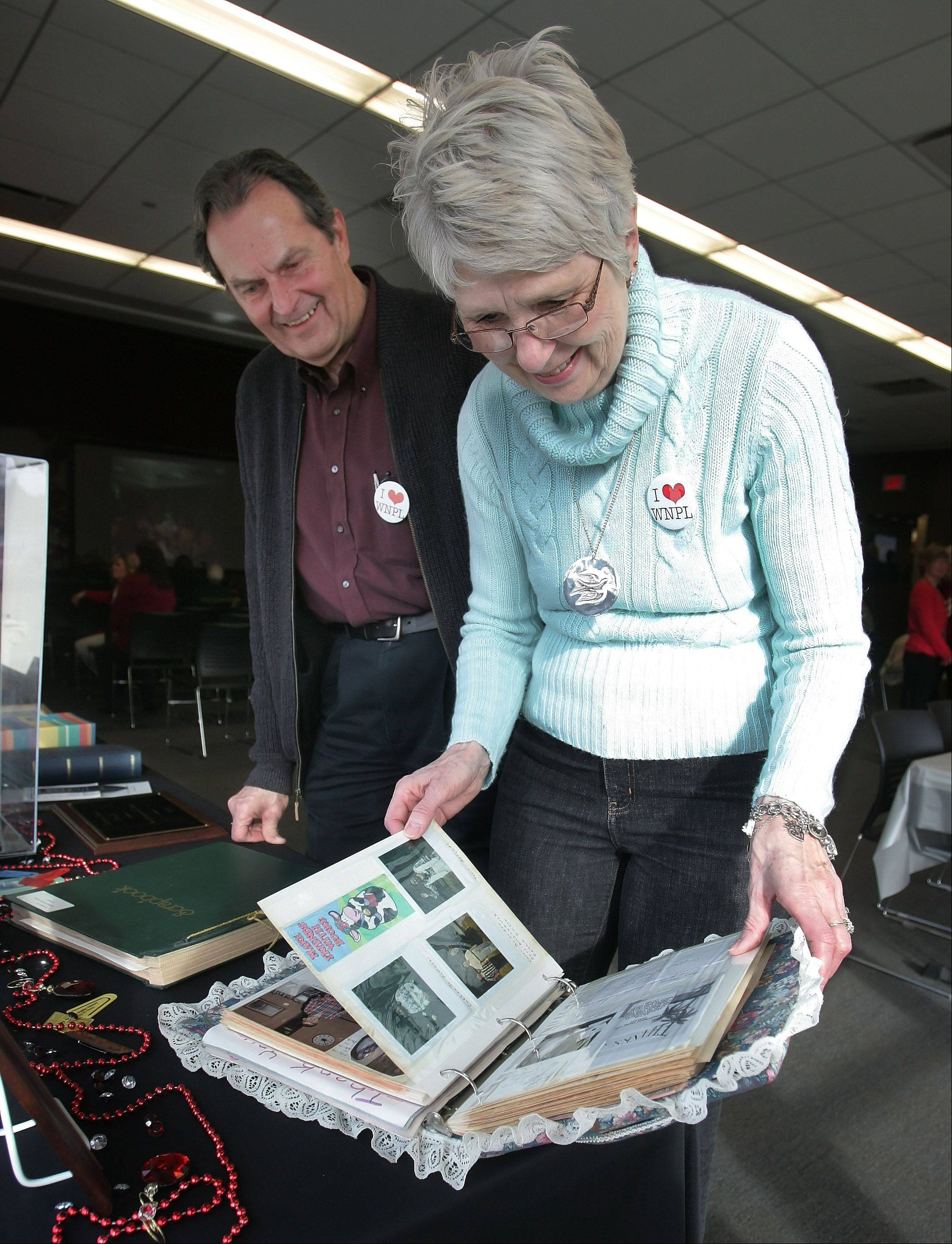 Trish and Ron Wendt, of Gurnee, look through scrapbooks on the history of the Warren-Newport Public Library library during the 40th anniversary celebration Sunday in Gurnee. The special event featured food, games and actives focused on the anniversary.