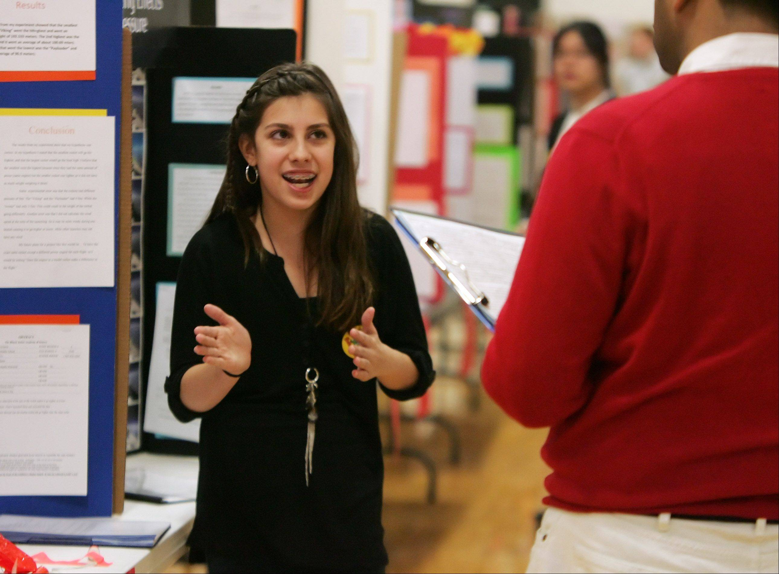 Maddie Pietranek describes her science project on model rockets and comparisons for distance with the judges during the judging of the 2013 Woodland Middle School seventh grade science fair Tuesday in Gurnee.