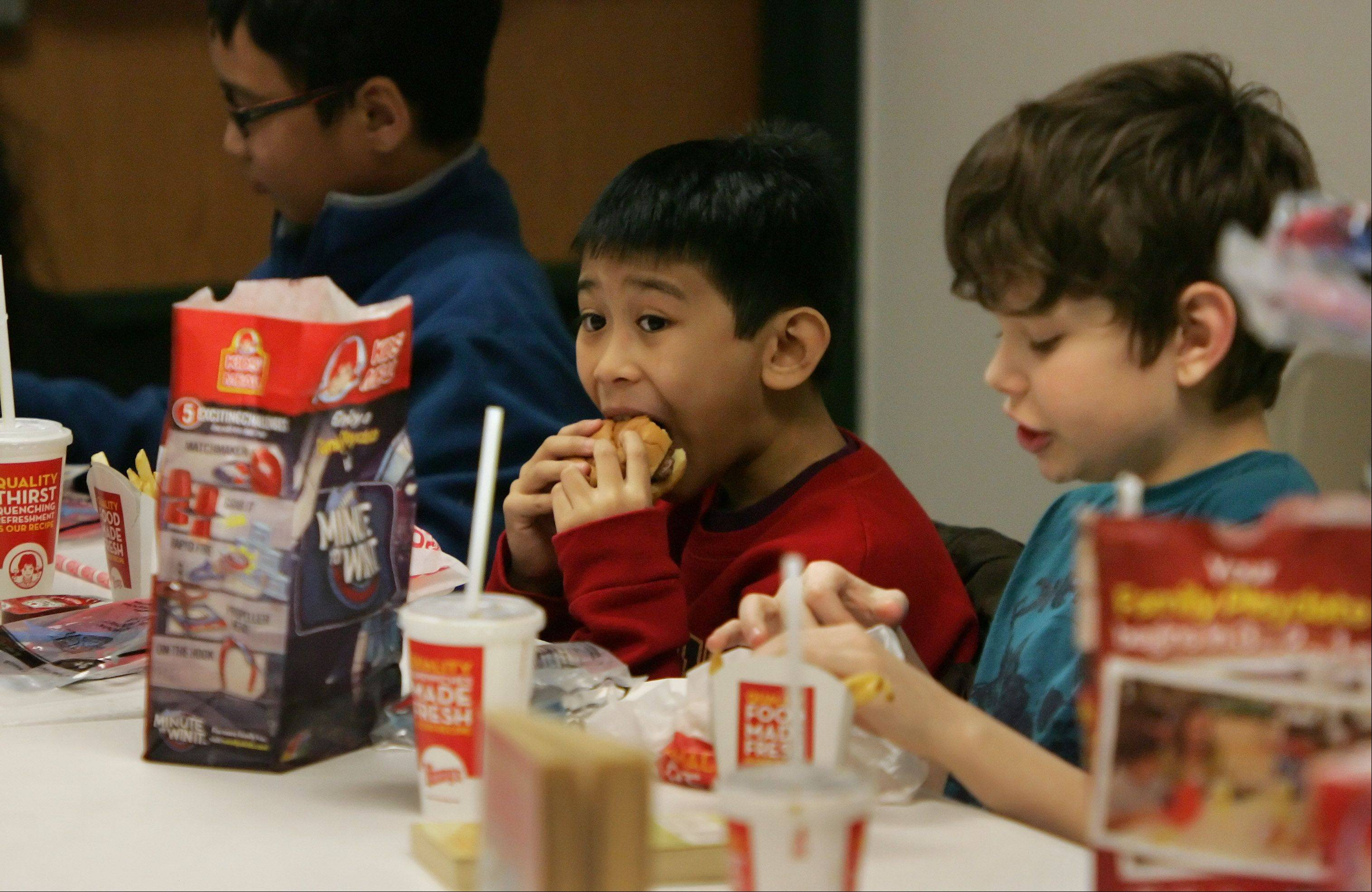 Fourth grader Gian Sarita enjoys a hamburger from Wendy's as students from Round Lake Beach Elementary School were treated to a free lunch for reading 550 books from Sept. 15 through Dec. 21 last year. The project was sponsored by the village, the Round Lake Area Exchange Club and Round Lake School District 116.