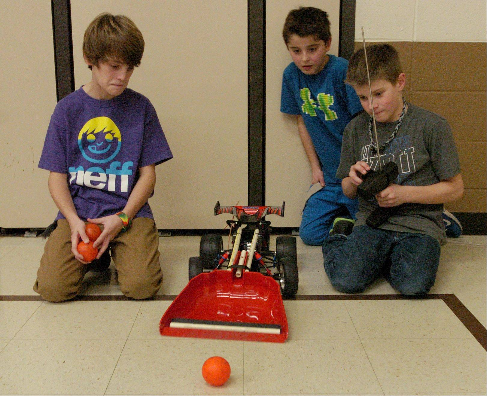 "Tyler Heinz, right, demonstrates his ""Remote Control Ball Retriever,"" to Jeremy Pones, left, and Nate Seminaro, center, during the 5th grade Invention Convention at Robert Crown School in Wauconda."