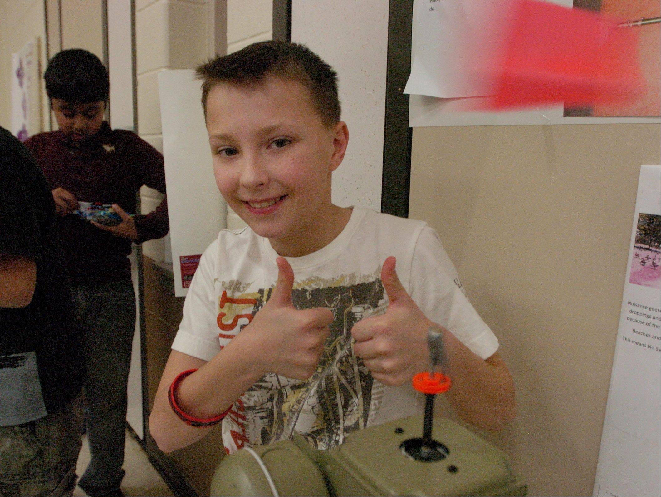 "Casey Zyskowski demonstrates his ""Geese-Be-Gone"" invention, designed to chase away geese by use of a motion detector, during the 5th grade Invention Convention at Robert Crown School in Wauconda."