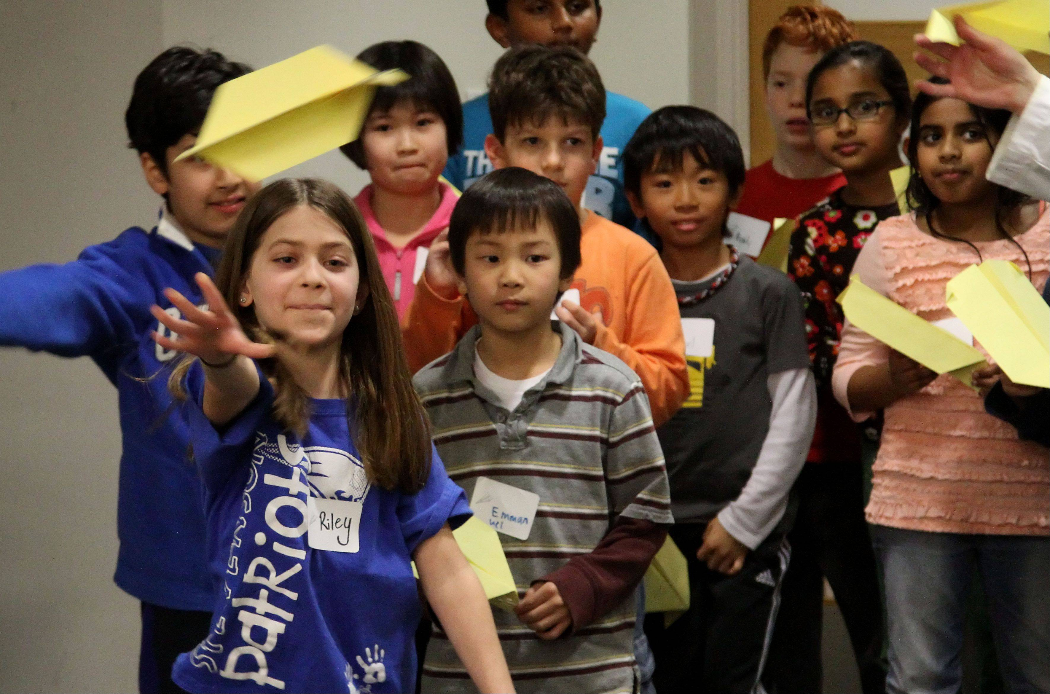 8-year-old Riley Heydenburg of Buffalo Grove launches a paper airplane during a program called Science Sleuths at Vernon Area Public Library.