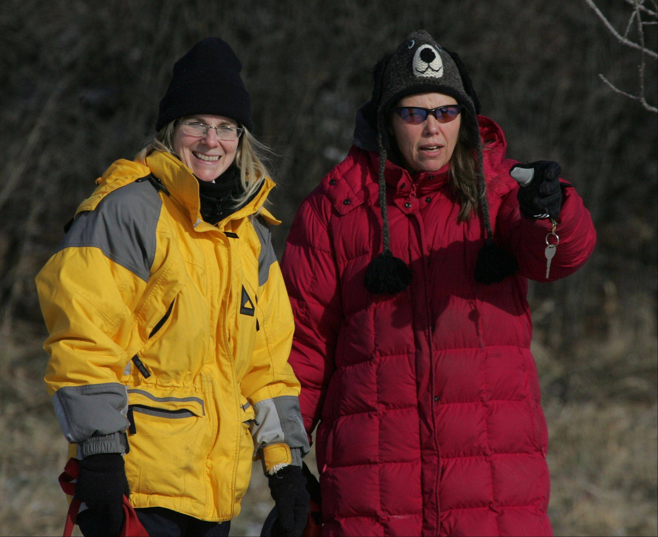 Patty Hanscom, of Ingleside, left, talks with Amy Payleitner, of Wildwood, as they watch their dogs play at the Lakewood Dog Exercise Area near Wauconda on one of the coldest days of the year in Lake County.