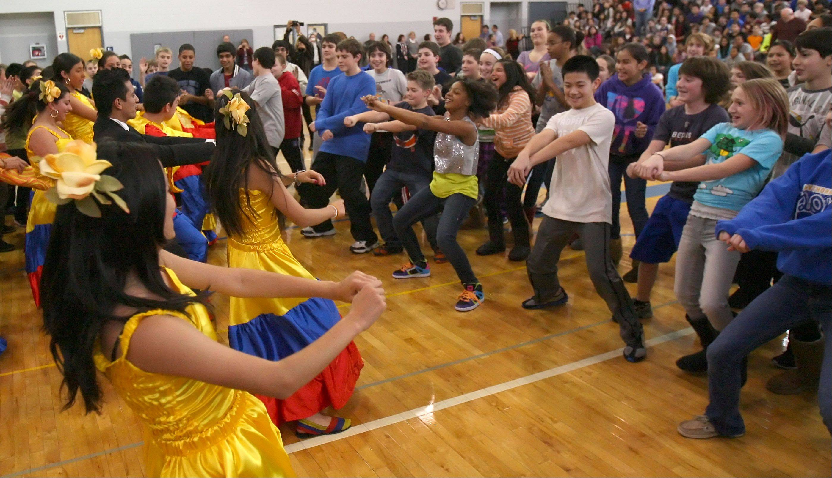 Students from the British Montessori School in Bogota, Columbia get students from Hawthorn Middle School South involved in a dance during an assembly at the school Thursday in Vernon Hills.