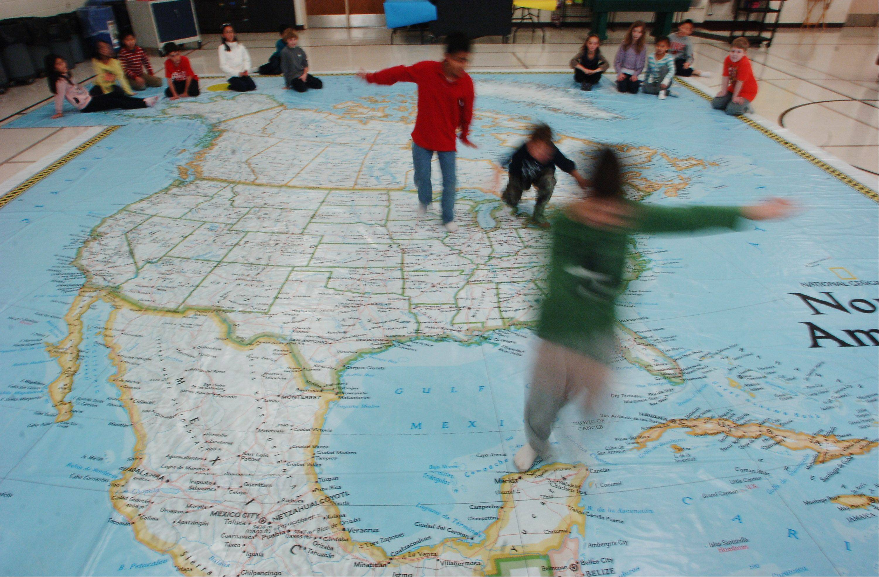 Fourth grade students at Half Day School in Lincolnshire find locations on a traveling National Geographic Giant Map of North America during a round of Simon Says Thursday. Third and fourth grade students have been using the map, which also comes with accessories, games, and books that assist the students in studying.