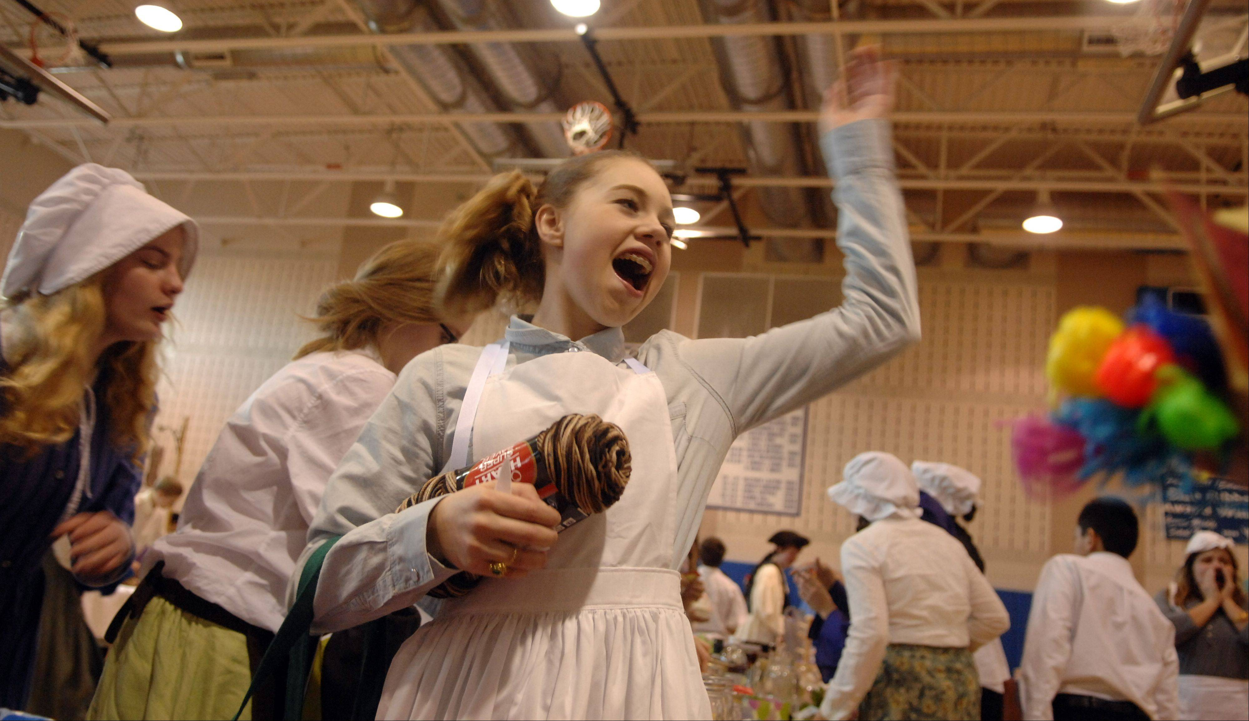 "Mackenzie Adkins tries to draw customers to her booth at the ""Shops Around the Green"" marketplace during the annual Patriots Day event at Geneva Middle School North Friday. Seventh-graders dressed up in costumes and incorporated their study of colonial life while enjoying a tournament of games, a marketplace and a stage presentation."