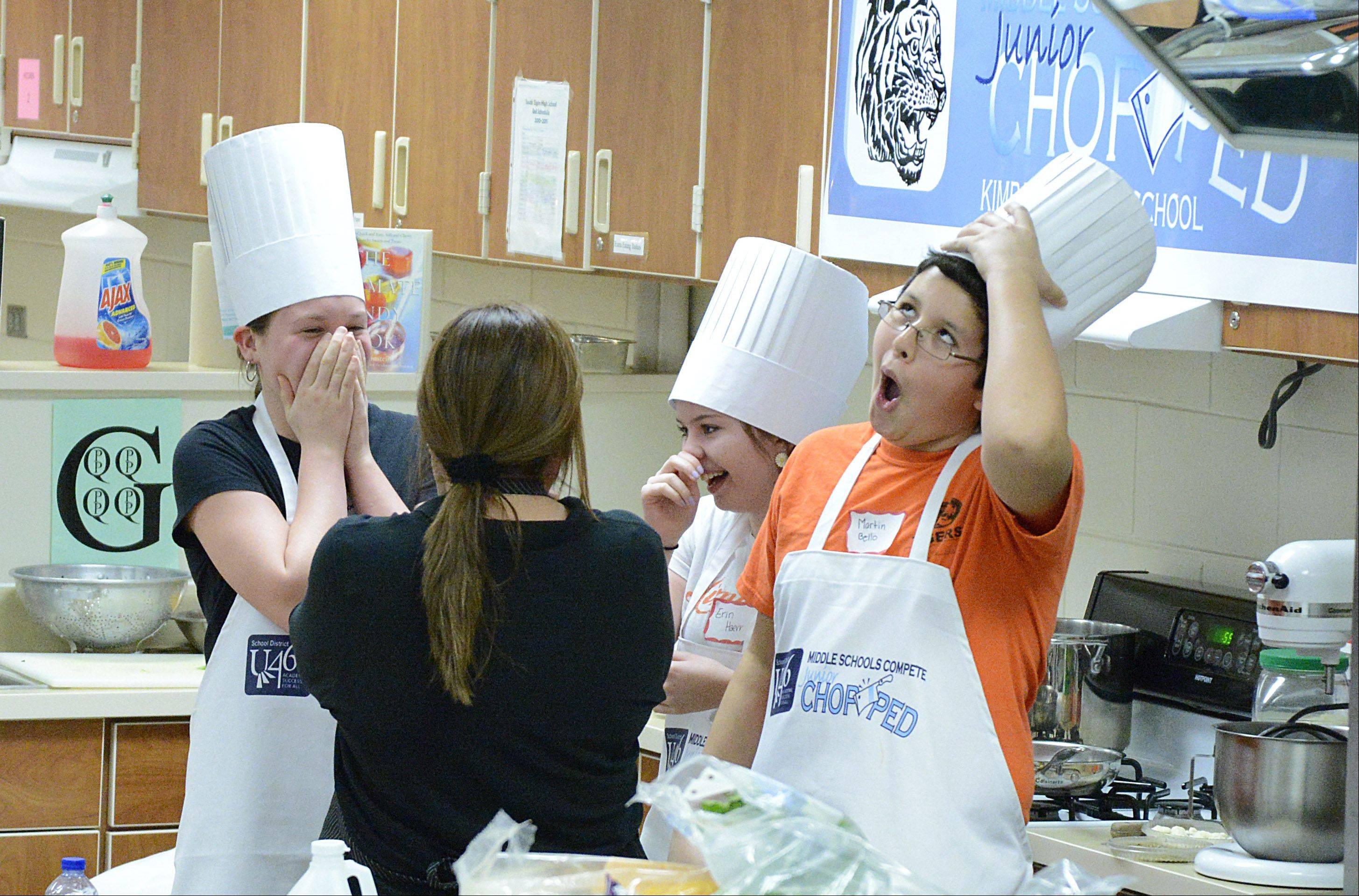 "The ""Swaggy Choppers"" team of Kimball Middle School, Allison Marsh, 13, Erin Haerr, 13, and Martin Bello, 14, react to being named the winners of the U-46 Junior Chopped competition at South Elgin High School on Saturday. The students, all of Elgin, rejoiced with their coach, Maria Martinez, back to camera, after taking the win with their Mediterranean and Italian themed lunch combo. Career and Technical Education and Nutrition Serves partnered for the event for Middle School FACS Rotation students to showcase their culinary skills at the competition based on the Food Network show, ""Chopped."""
