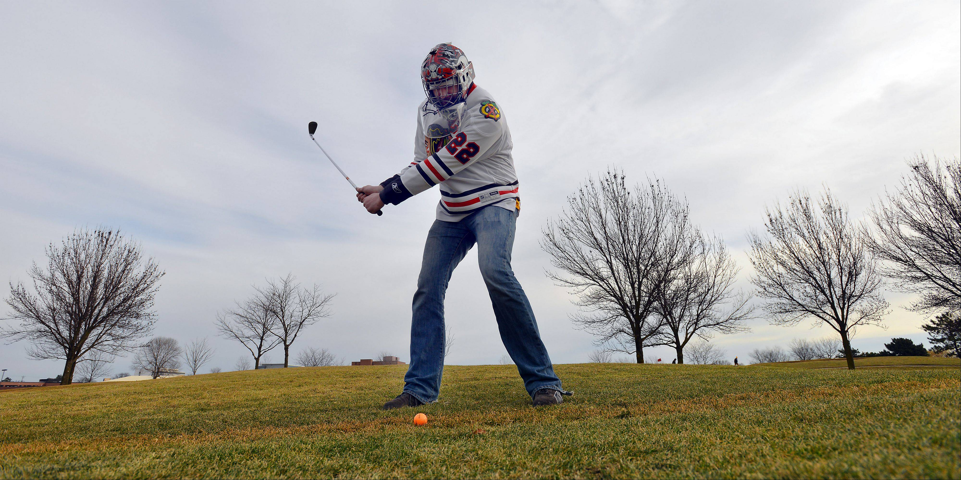 Wearing a Chicago Blackhawks hockey goalie mask, Scott Johnson, of Arlington Heights, is excited to have hockey back but wanted to partake in the annual chilly golf at Arlington Lakes Golf course on Saturday.