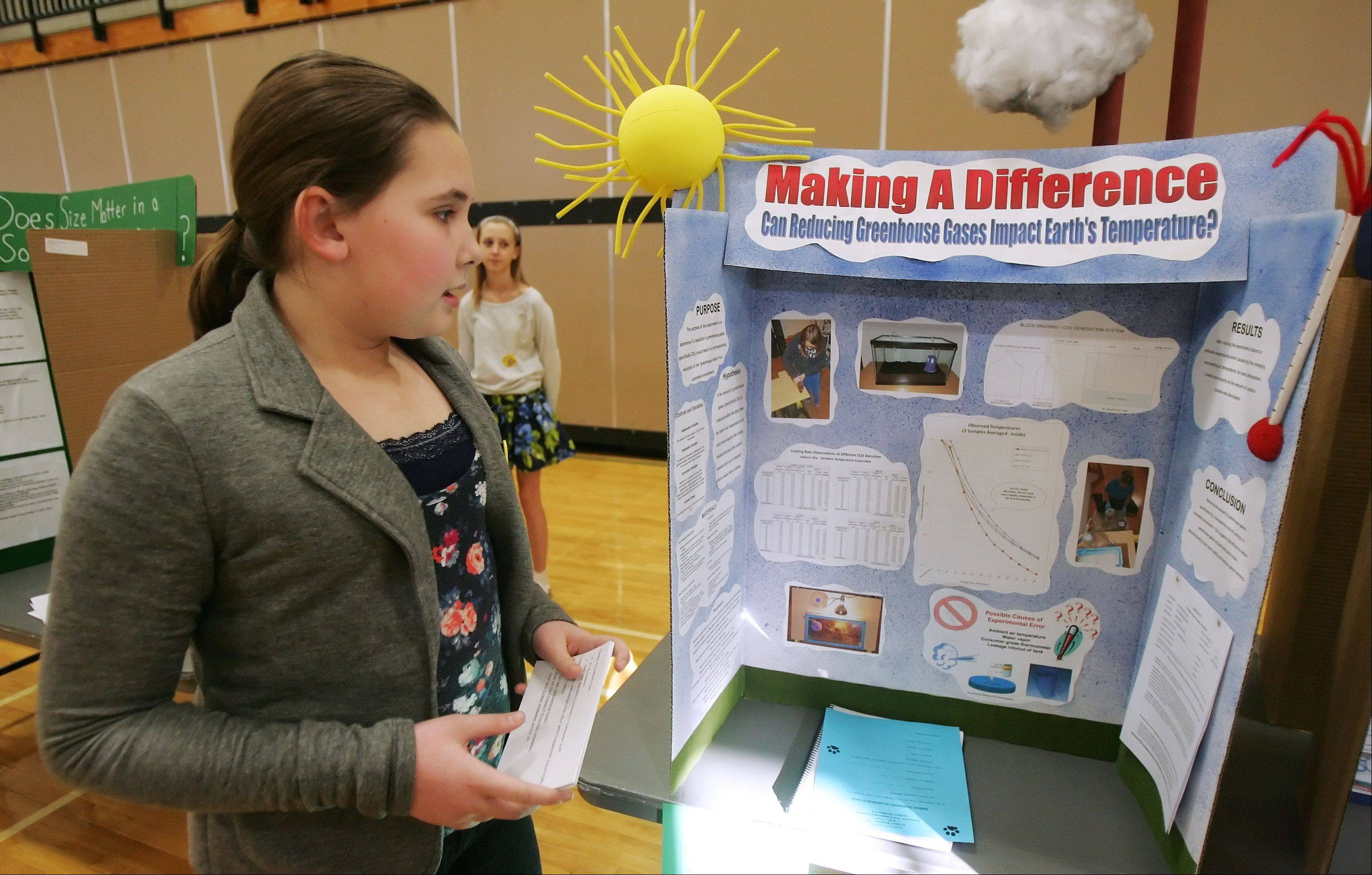 Kathryn Larson explains how she made a carbon dioxide generator to test her theories on global warming and its affects on the Earth during the judging of the 2013 Woodland Middle School seventh grade science fair in Gurnee.