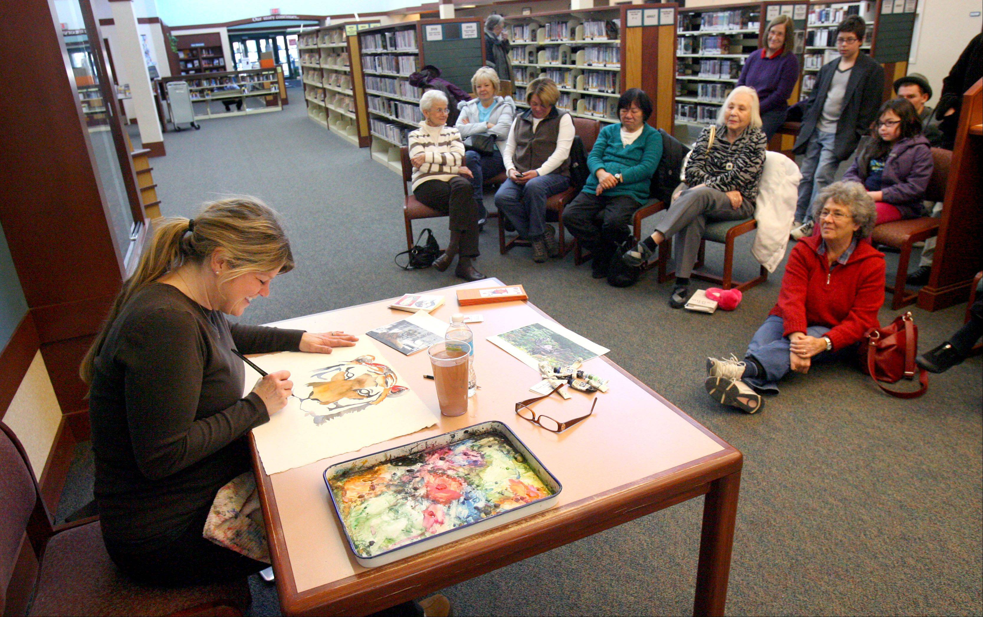 Water color artist Julie Adriansen of Lake Villa drew a small crowd as she shared her painting skills during Lake Villa District Library's Artist in Residence program Monday.