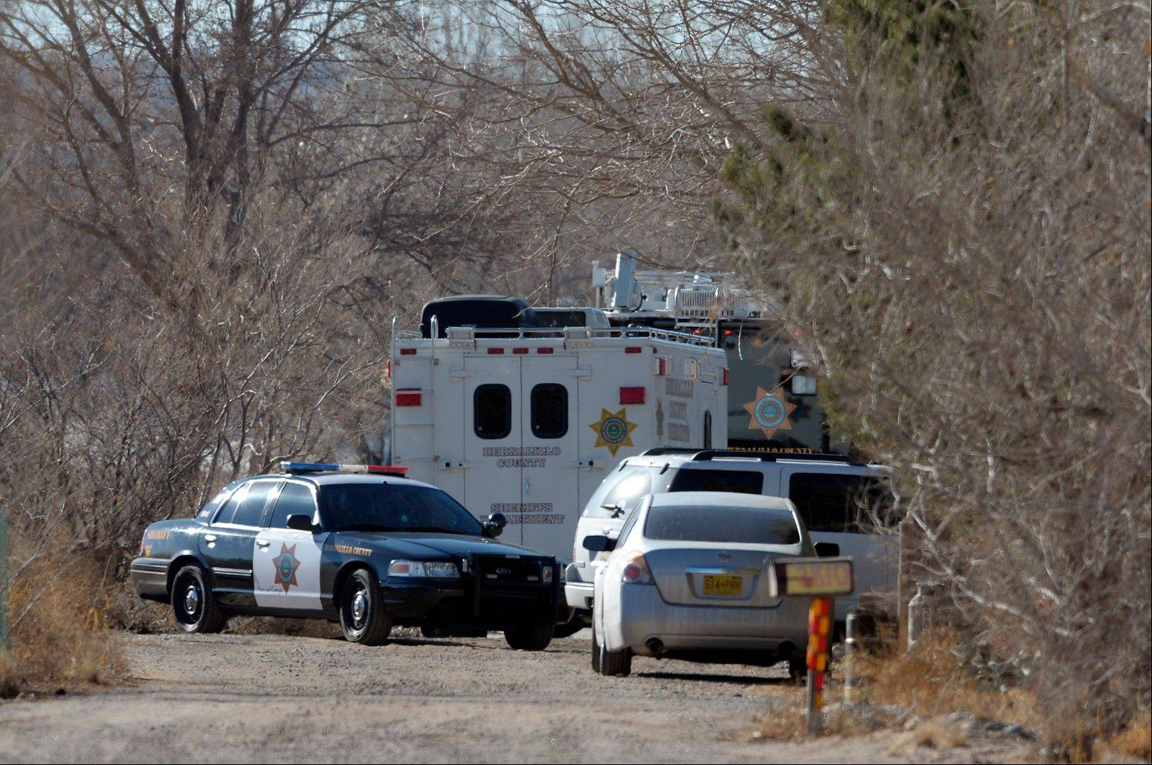 Deputies and crime scene personnel work the scene of a mass shooting near Albuquerque, N.M., Sunday. Authorities said a teenage boy fatally shot two adults and three children at a rural home.