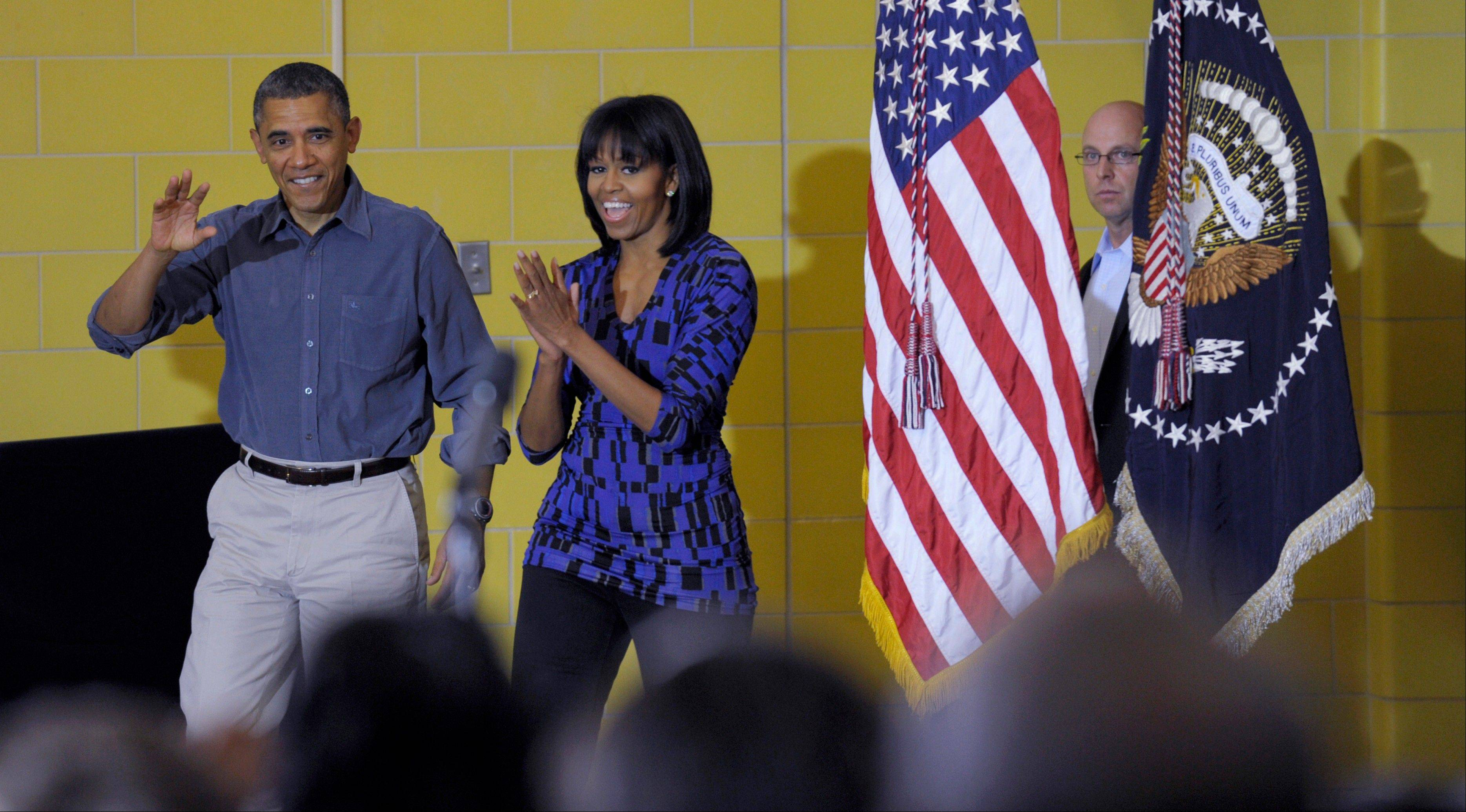 President Barack Obama and first lady Michelle Obama arrive prior to speaking at Burrville Elementary School in Washington, Saturday, Jan. 19, 2013, after the first family participated in a community service project for the National Day of Service as part of the 57th Presidential Inauguration.