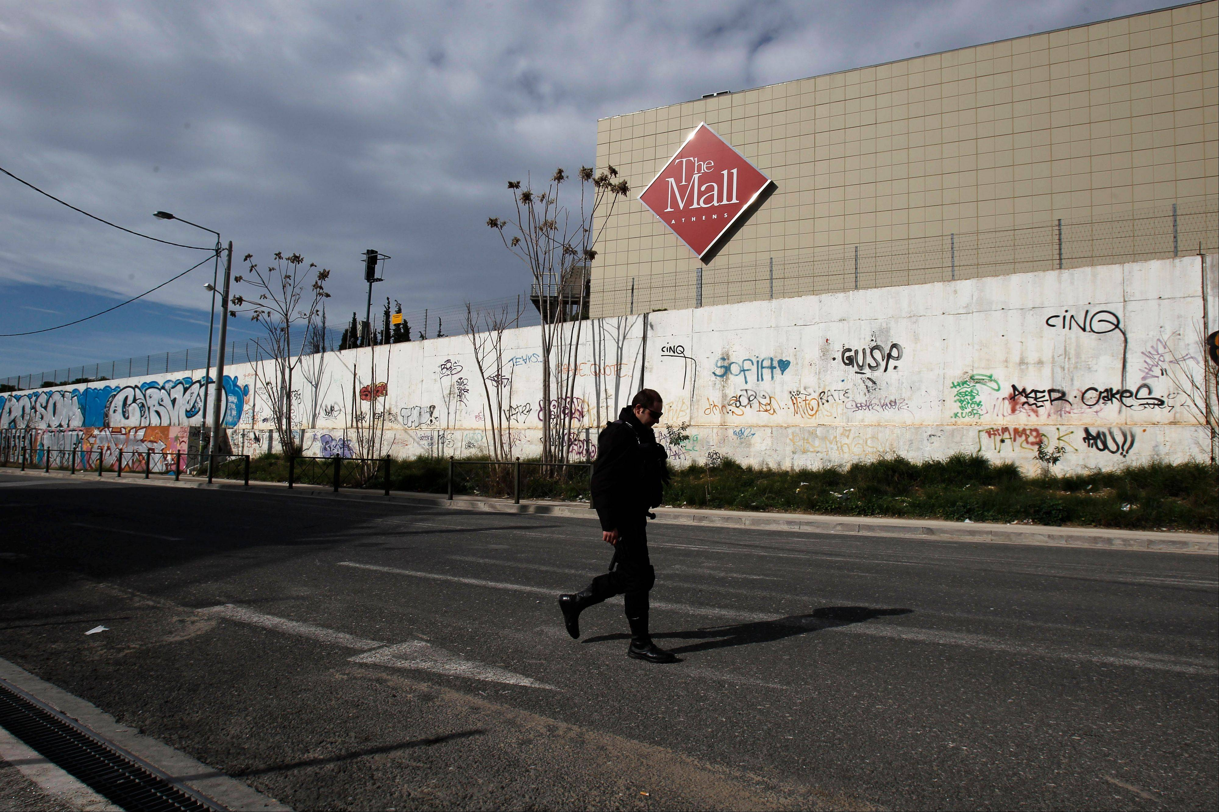 A police officer secures the street in front of a mall following a blast in Athens, Sunday, Jan. 20 2013. A bomb exploded Sunday at a shopping mall in Athens, slightly wounding two security guards, police said.
