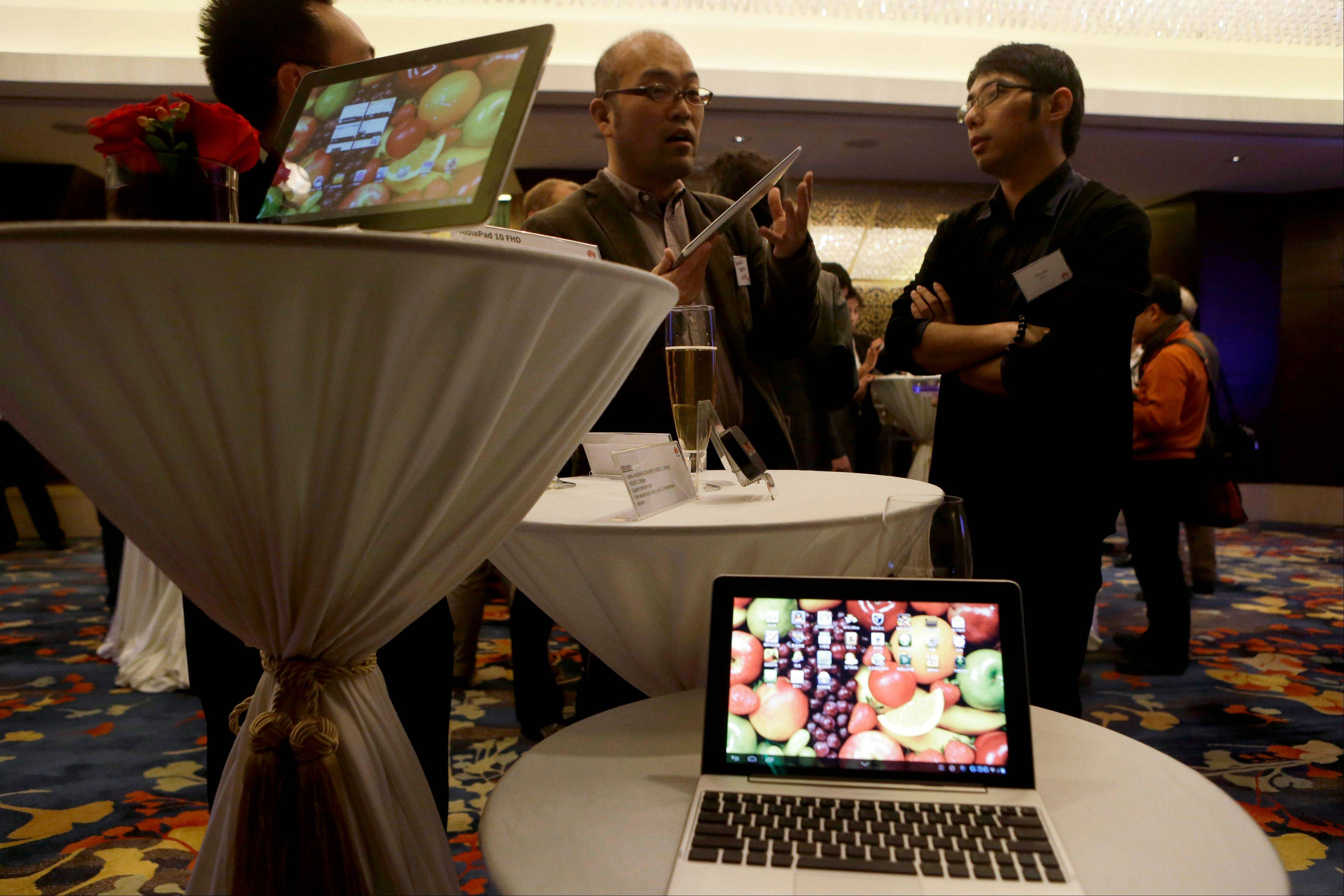 Huawei staff member, right, talks to journalists near laptops and tablets manufactured by Huawei during a media event at a hotel in Beijing .