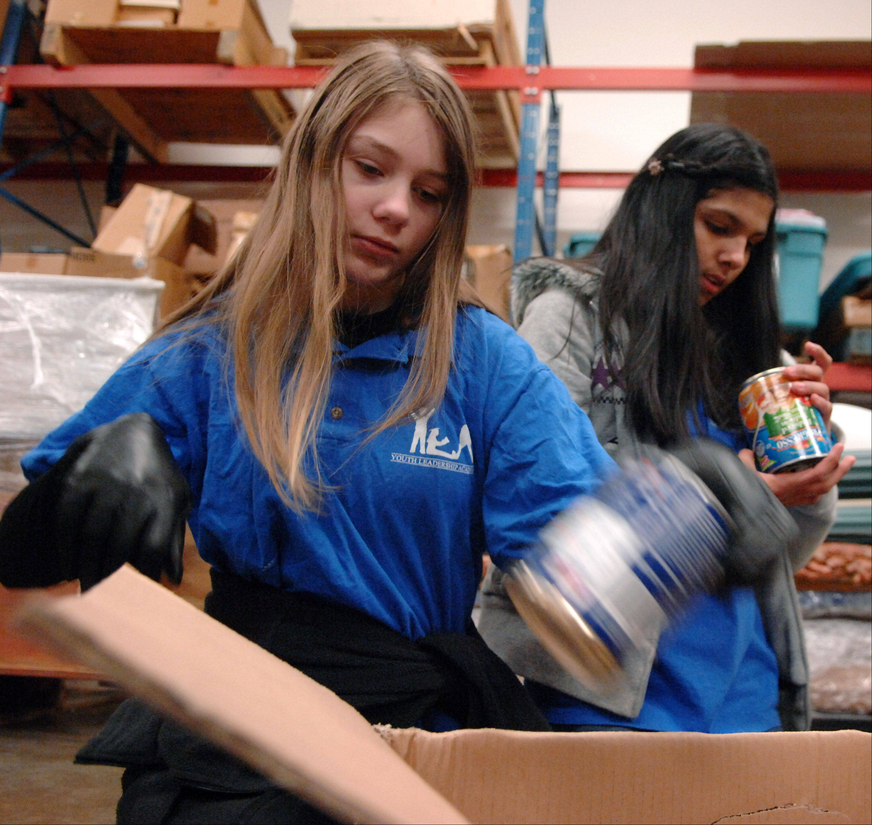 Dundee-Crown freshman Amanda Craig, left, and Carpentersville Middle School seventh-grader Elsie Guerra check expiration dates as donated food arrives Monday at the Church of the Brethren general offices in Elgin. Members of the Elgin Youth Leadership Academy collected and sorted food that was to be delivered to six local food pantries, with half of it going to Food for Greater Elgin.