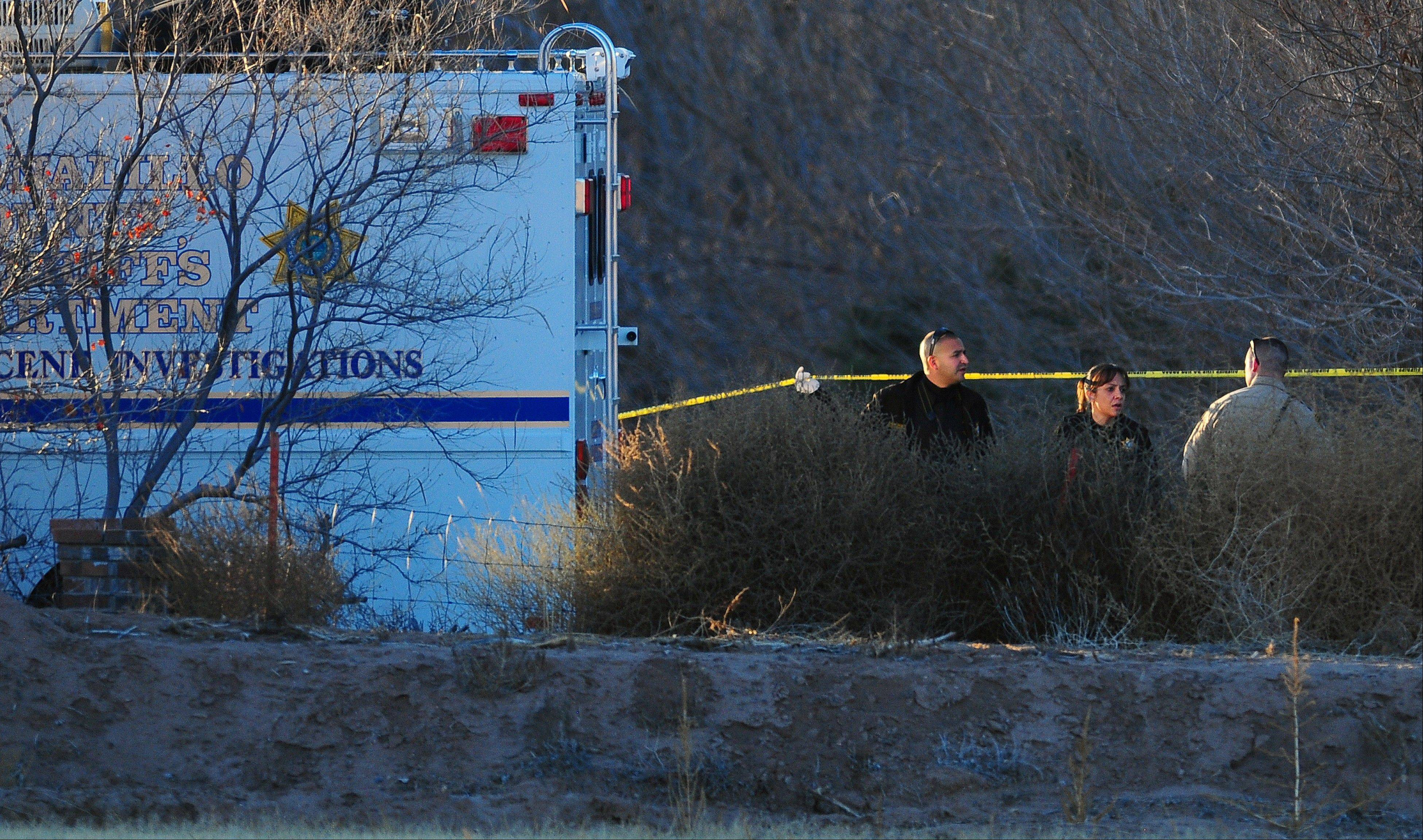 Bernalillo Sheriff Deputies investigate at the scene of the multiple homicide near Albuquerque, N.M., Sunday. A 15-year-old boy was in custody following the shooting deaths the teen�s parents and three young children, all of whom were found dead in a New Mexico home.