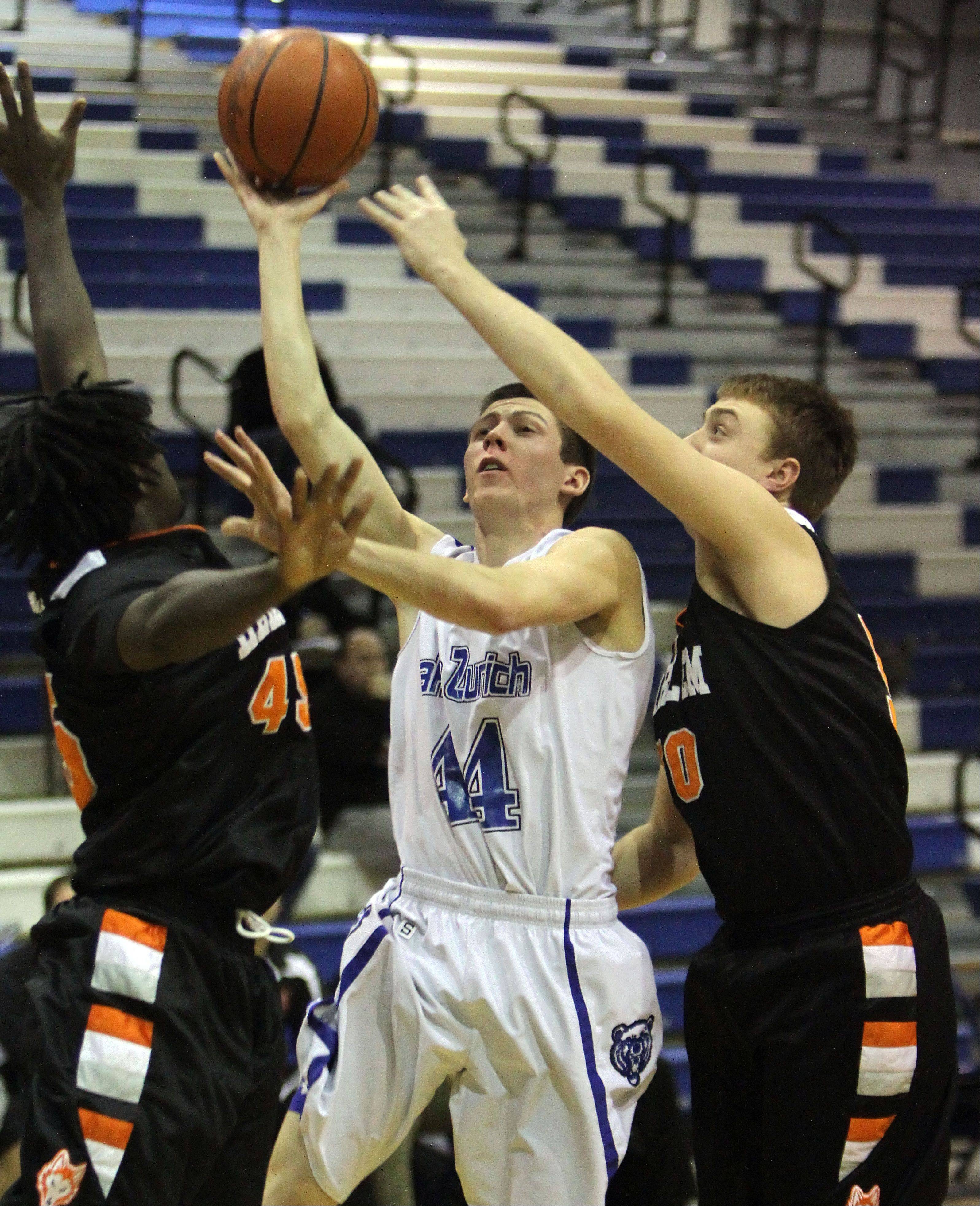 Lake Zurich�s Ryan Roach drives on Brent Croft, left, and Harlem on Monday night at Lake Zurich.