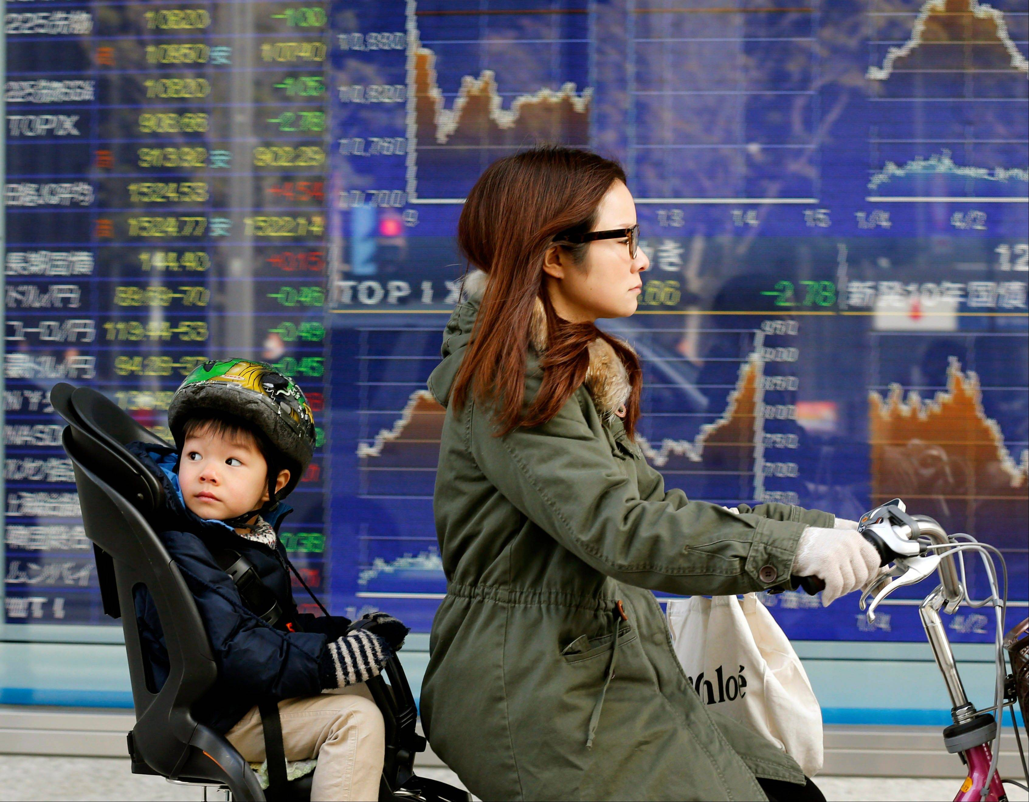 A mother and child cycle past an electronic stock board of a securities firm in Tokyo, Monday.