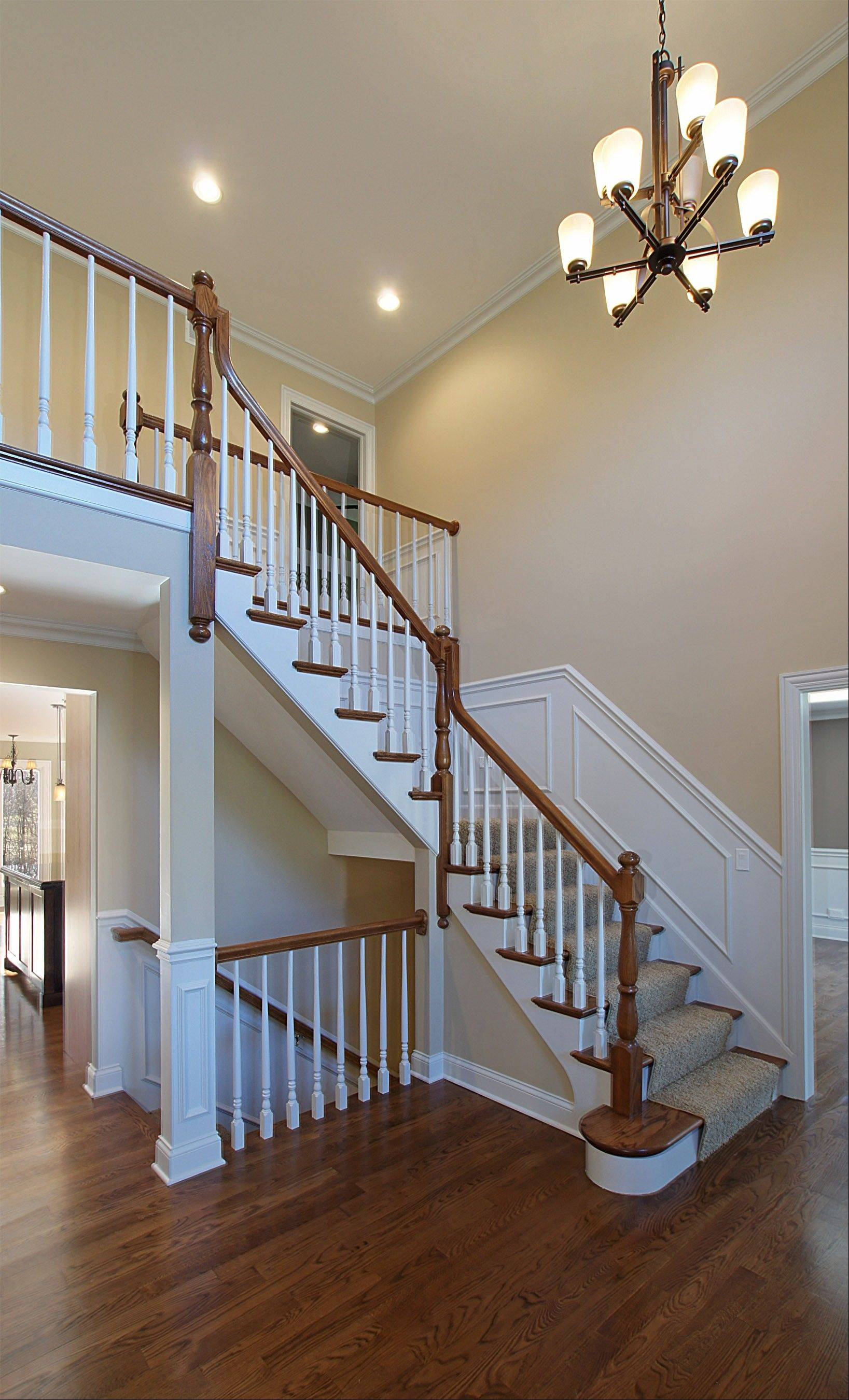 A staircase and two-story foyer welcome guests to the home.