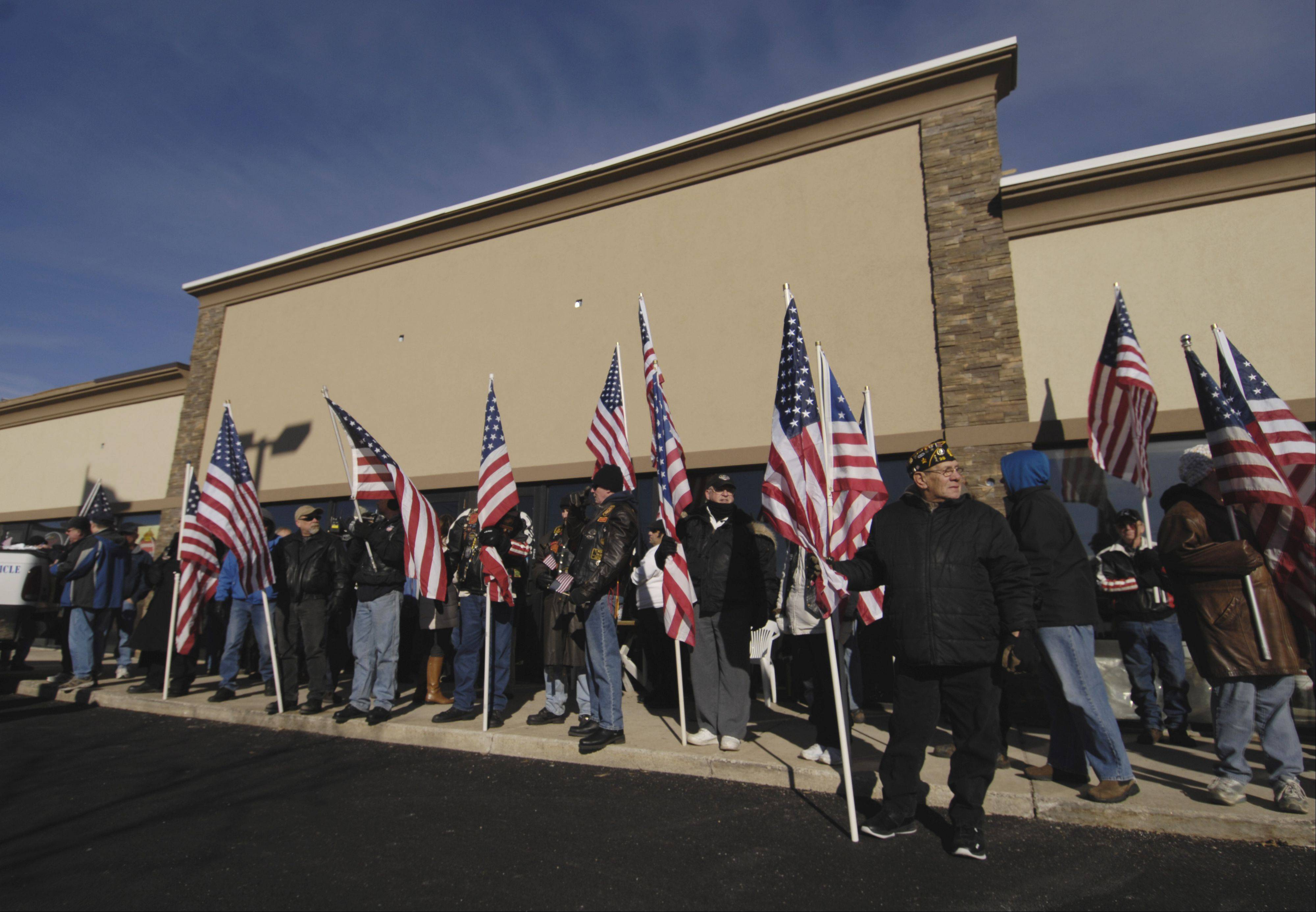 Supporters of the Glendale Heights VFW Post 2377 hold a rally yesterday in response to Midland Realty and Development's demand that the VFW stop flying the American and POW/MIA flags in front of their hall on Army Trail Road. The post has been flying a flag at the location since 1991.