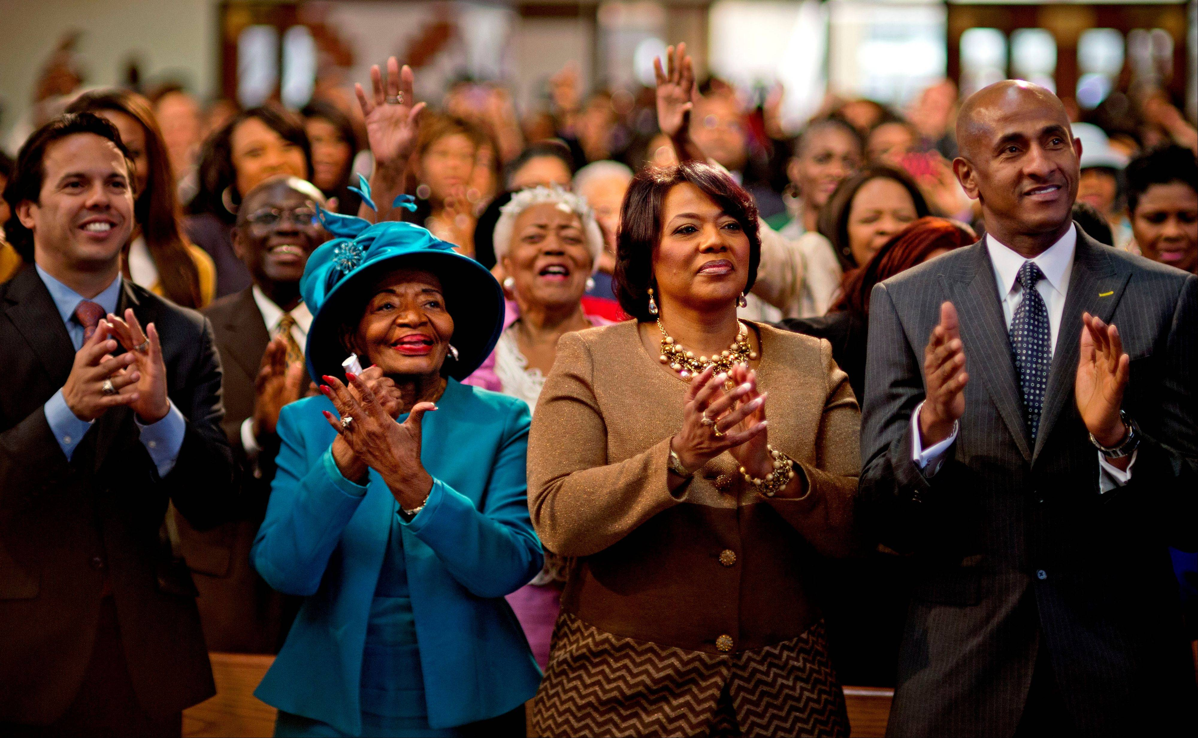 Bernice King, center right, and Christine King Farris, center left, the daughter and sister of Dr. Martin Luther King Jr., applaud while watching a broadcast as President Barack Obama is inaugurated following the Dr. Martin Luther King Jr. holiday commemorative service at the Ebenezer Baptist Church in Atlanta Monday, Jan. 21, 2013.