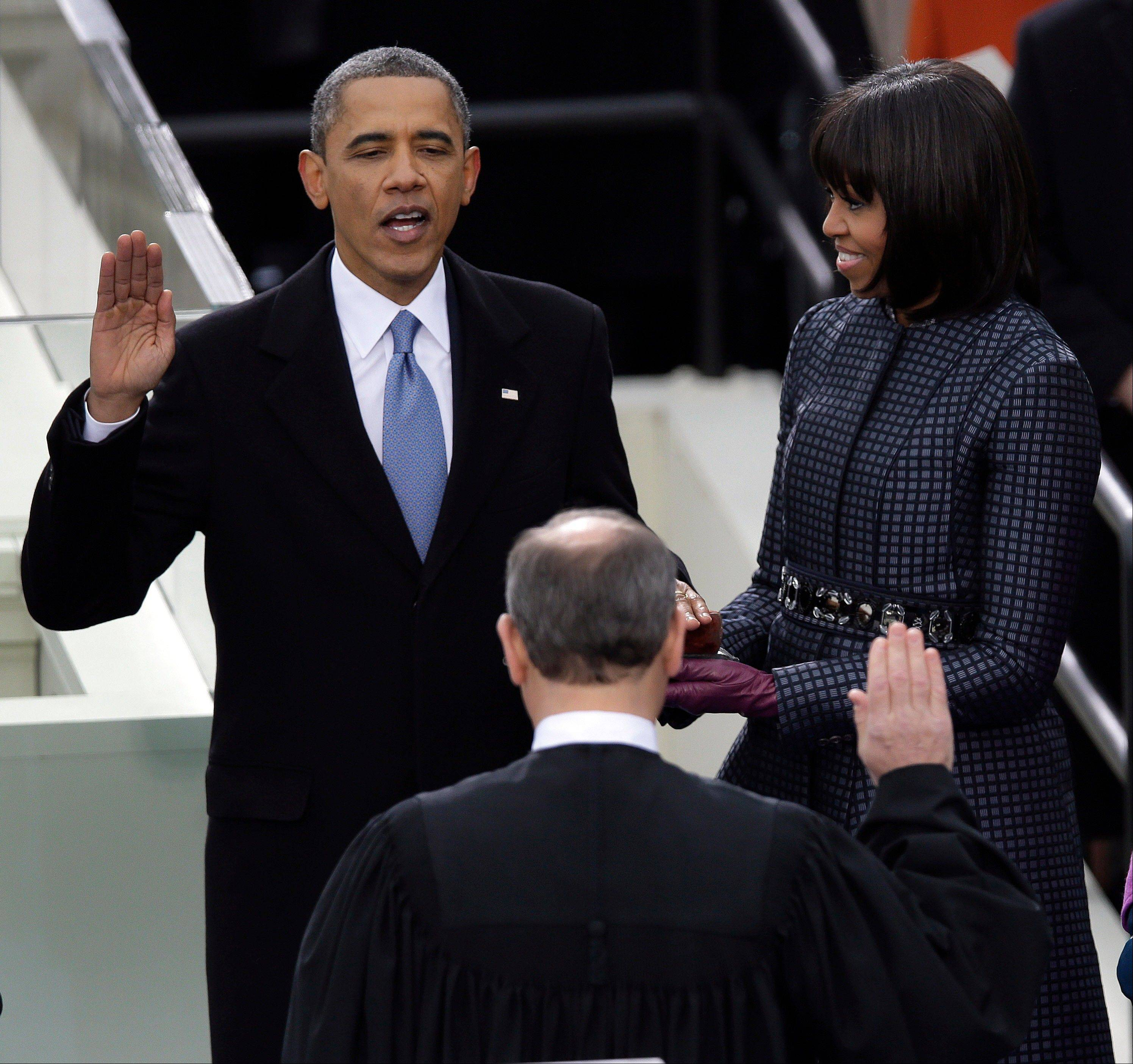 President Barack Obama receives the oath of office from Chief Justice John Roberts as first Lady Michelle holds the bible at the ceremonial swearing-in at the U.S. Capitol during the 57th Presidential Inauguration in Washington, Monday, Jan. 21, 2013.