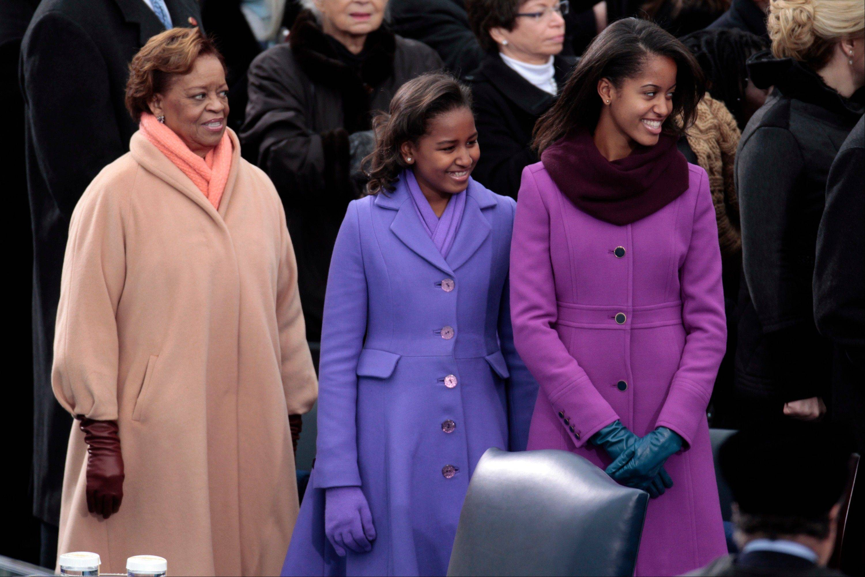 Marian Robinson, mother of first lady Michelle Obama, left, stands with her granddaughters Sasha Obama, center, and Malia Obama during the U.S. presidential inauguration at the Capitol in Washington, D.C., U.S., on Monday, Jan. 21, 2013. As he enters his second term President Barack Obama has shed the aura of a hopeful consensus builder determined to break partisan gridlock and adopted a more confrontational stance with Republicans.