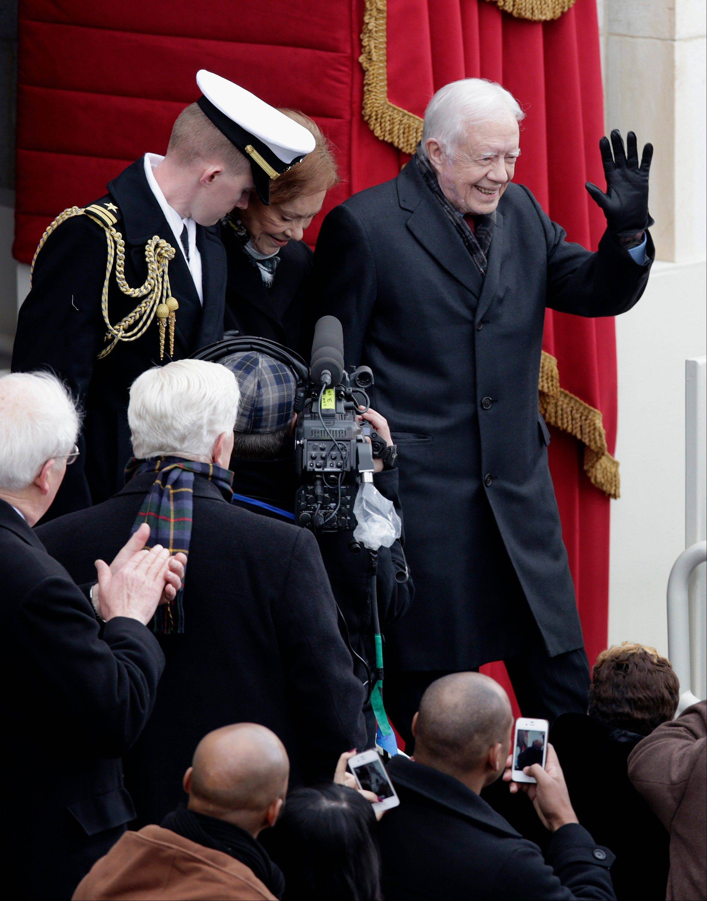 Former U.S. President Jimmy Carter, right, waves while arriving with his wife Rosalynn Carter, center, during the presidential inauguration in Washington, D.C., U.S., on Monday, Jan. 21, 2013.