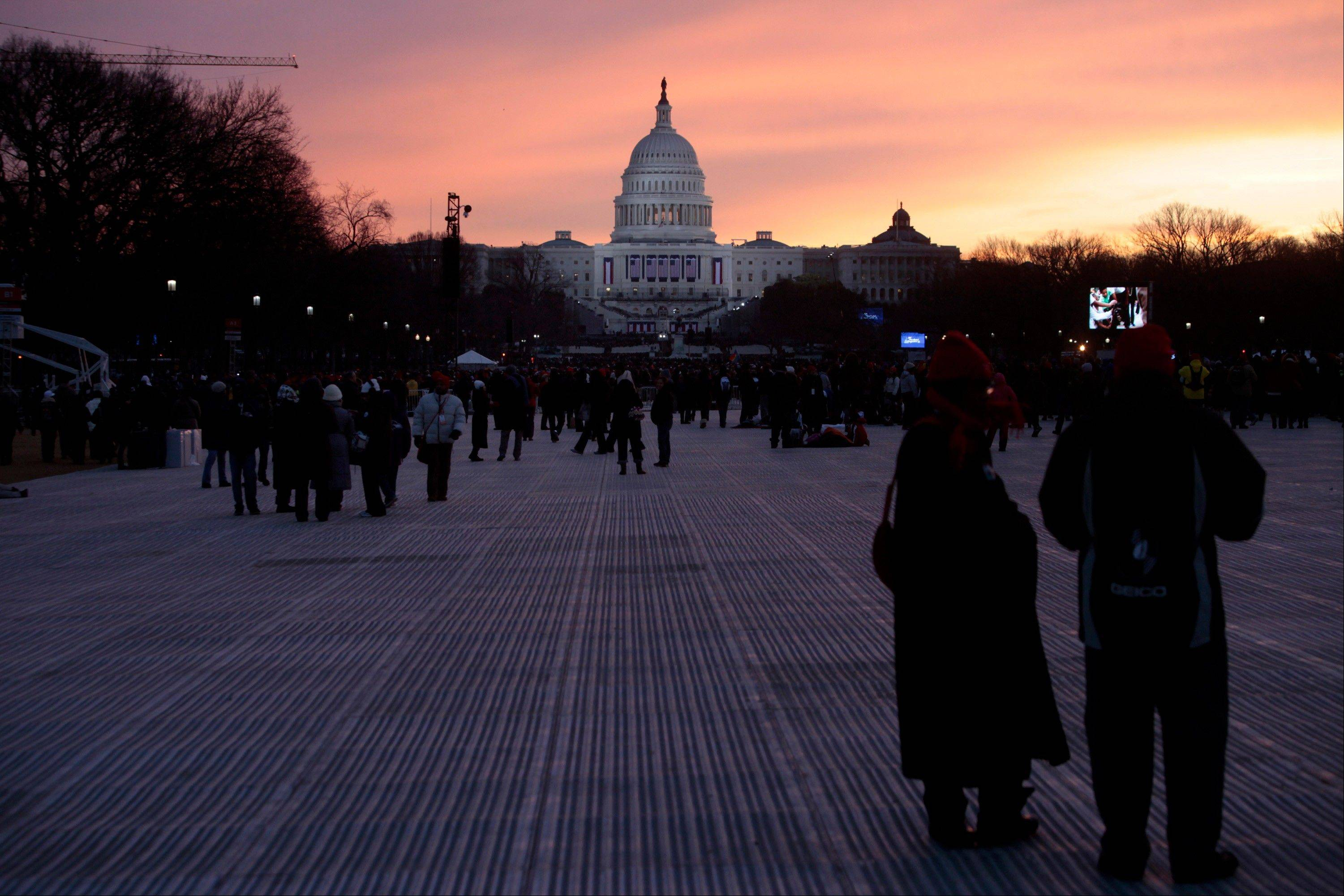 The sun rises as attendees gather in front of the Capitol building before the start of the U.S. presidential inauguration in Washington, D.C., U.S., on Monday, Jan. 21, 2013.