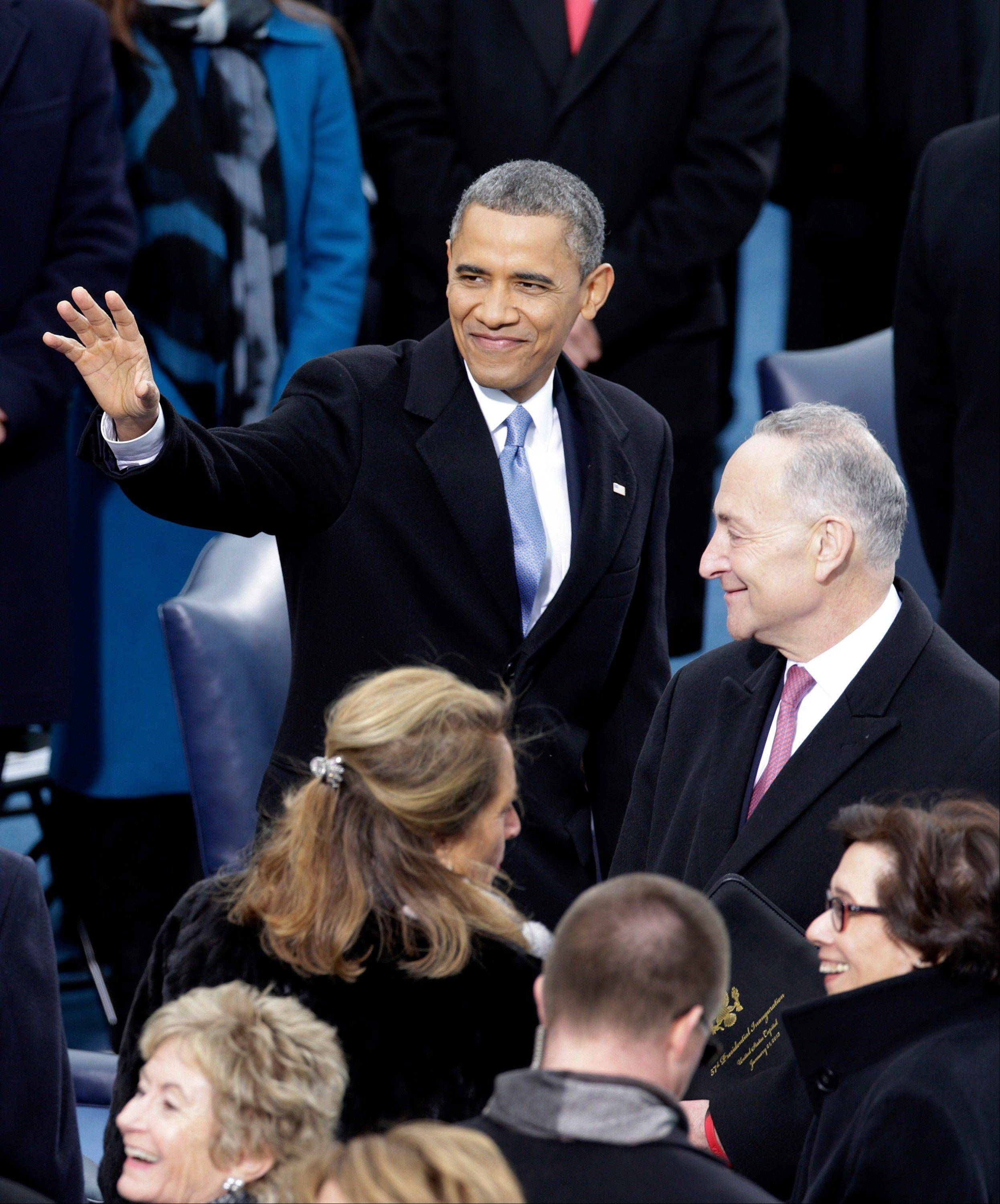 U.S. President Barack Obama, left, waves as Senator Charles Schumer, a Democrat from New York, looks on while arriving during the presidential inauguration in Washington, D.C., U.S., on Monday, Jan. 21, 2013.