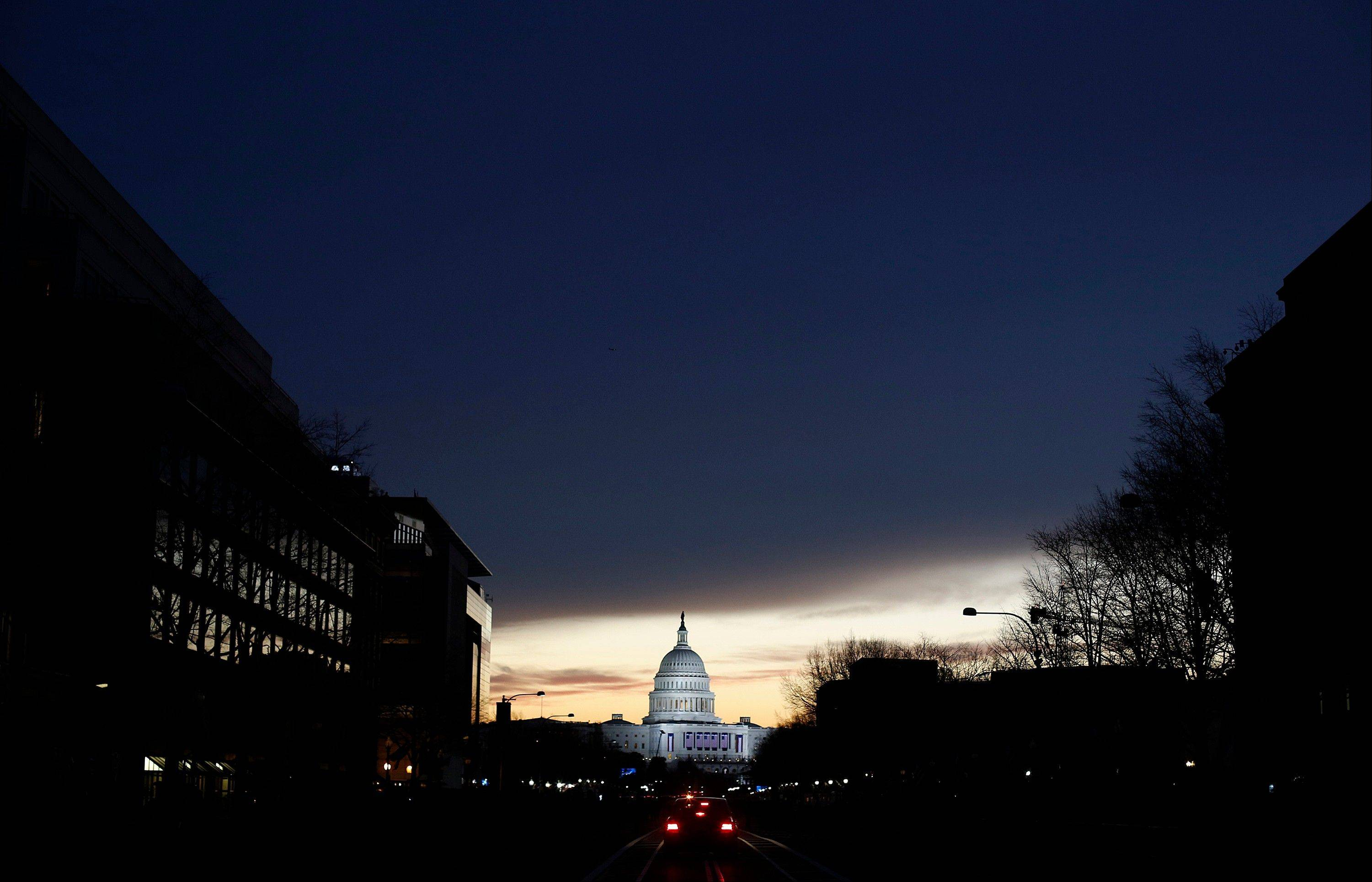 The sun rises behind the Capitol building before the start of the U.S. presidential inauguration in Washington, D.C., U.S., on Monday, Jan. 21, 2013.