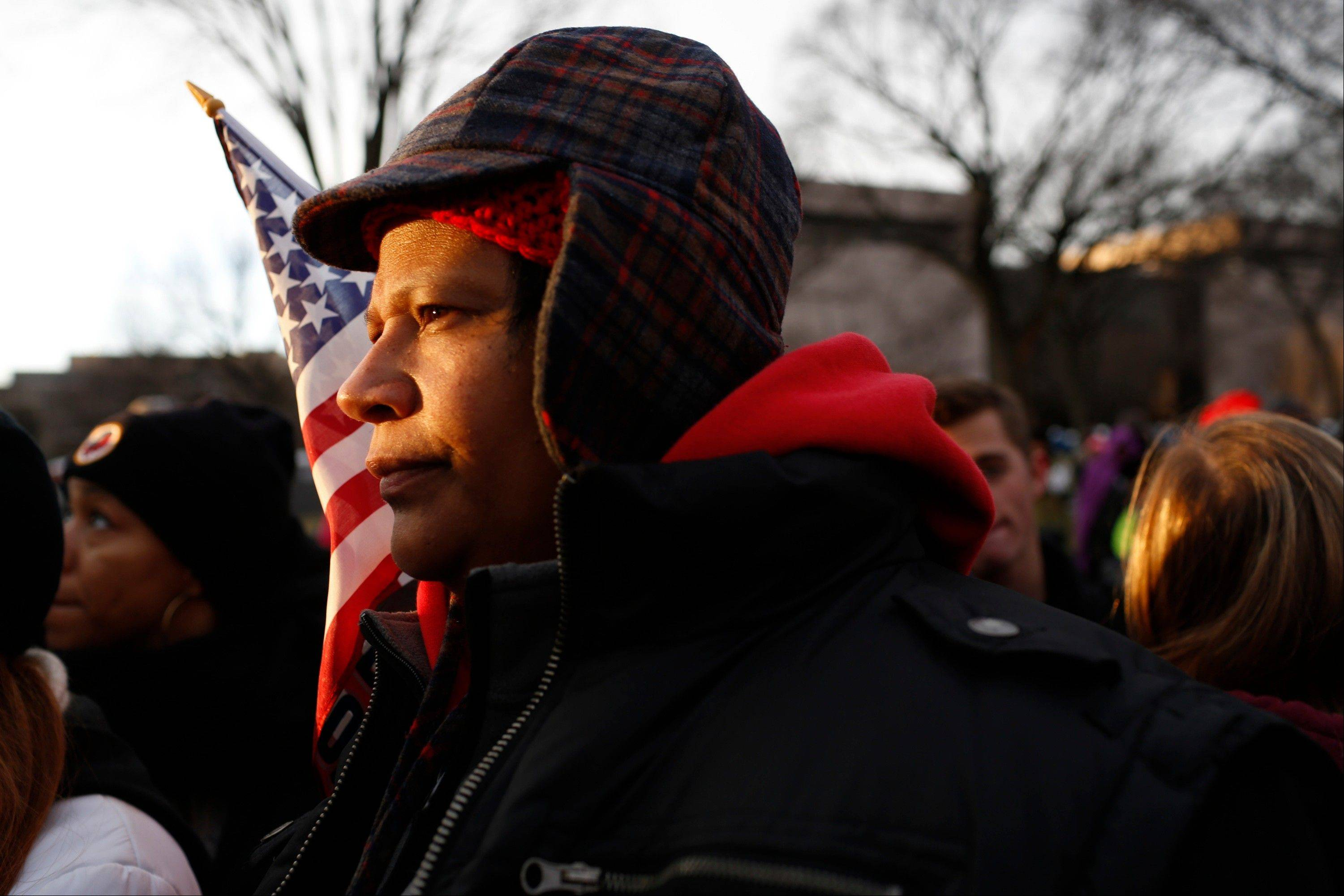 The sun shines on the face of an attendee before the start of the U.S. presidential inauguration in Washington, D.C., U.S., on Monday, Jan. 21, 2013.