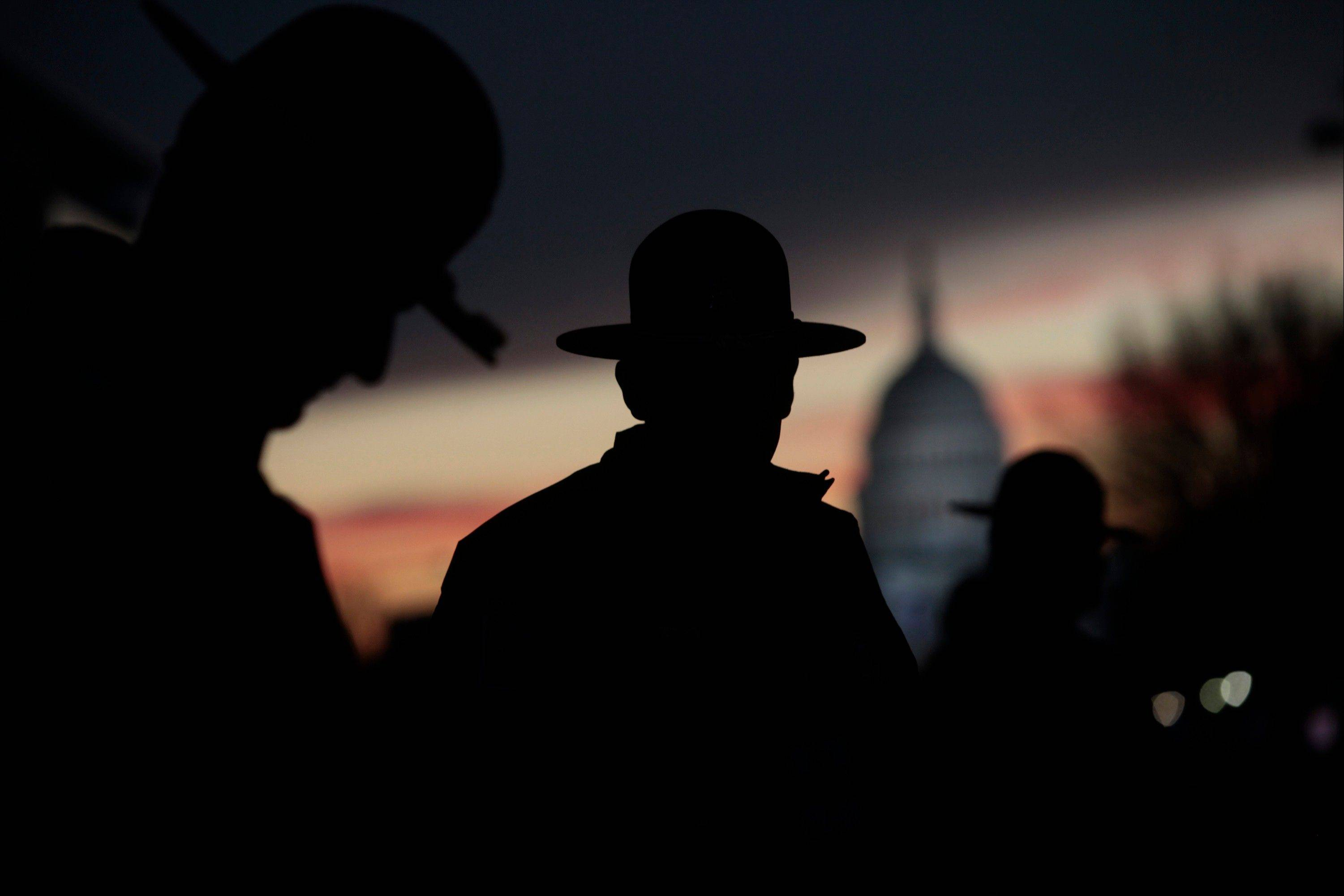 The silhouettes of Minnesota State Troopers are seen as the sun rises before the start of the U.S. presidential inauguration in Washington, D.C., U.S., on Monday, Jan. 21, 2013.
