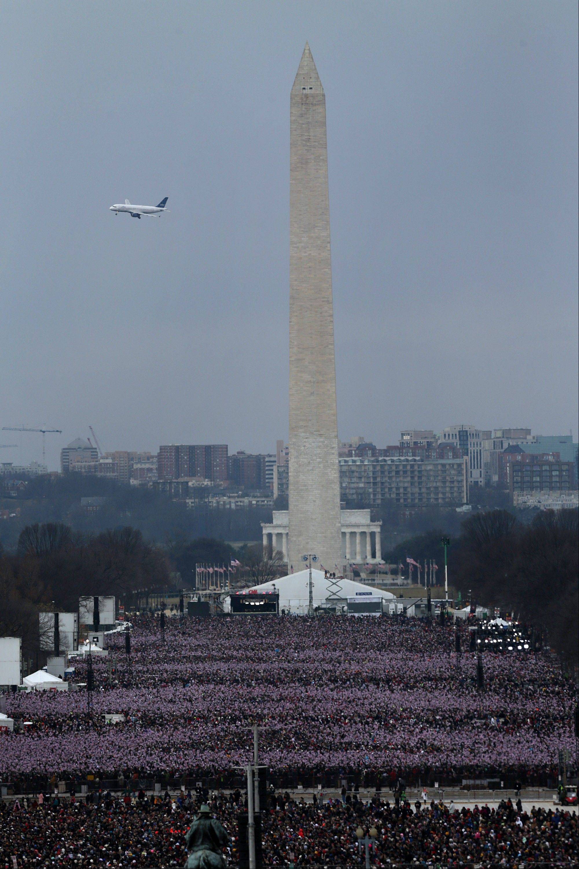 A plane flies overhead as attendees gather near the Washington monument during the U.S. presidential inauguration in Washington, D.C., U.S., on Monday, Jan. 21, 2013.