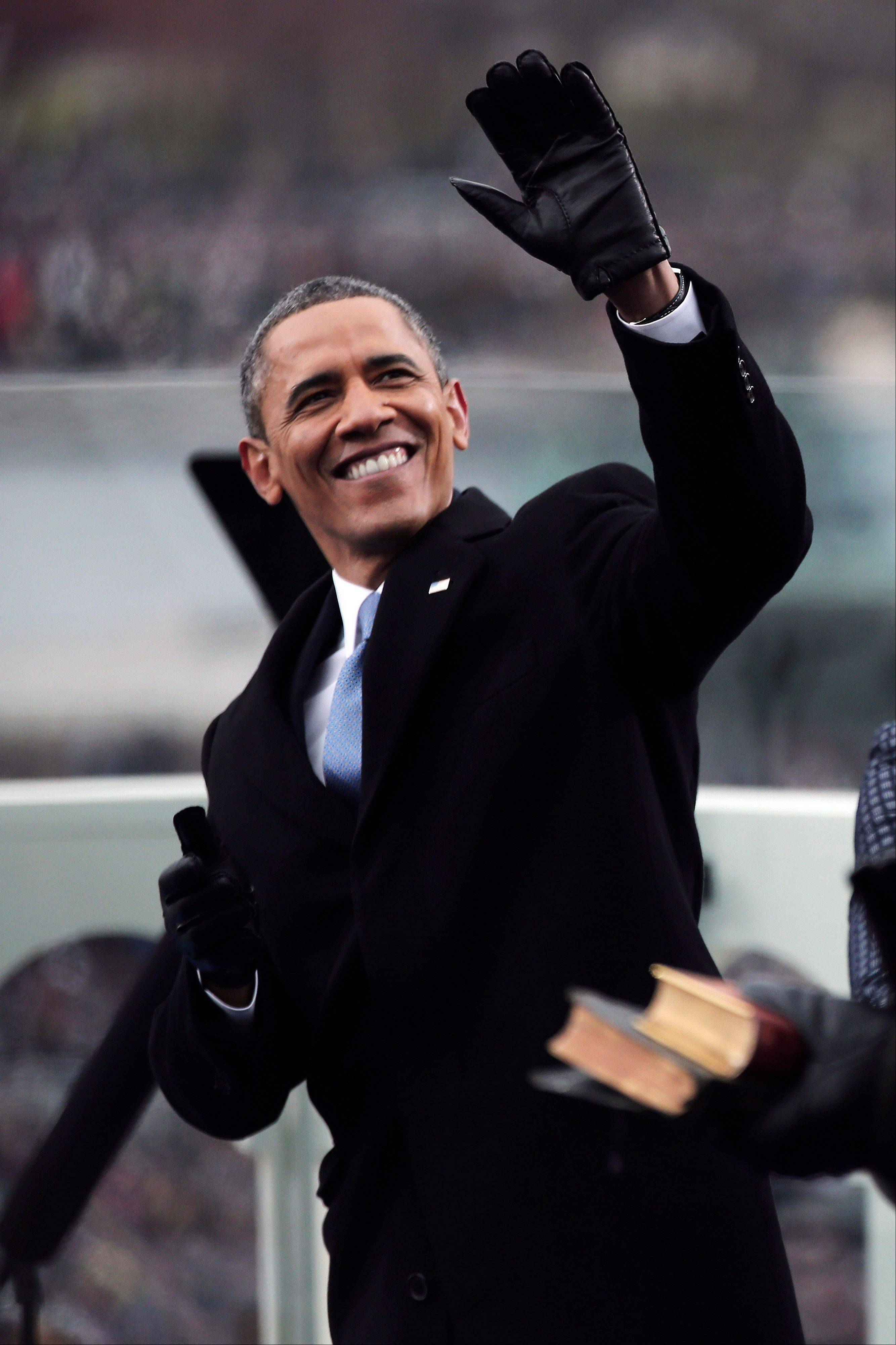 President Barack Obama' waves on the West Front of the Capitol in Washington, Monday, Jan. 21, 2013, prior to his ceremonial swearing-in ceremony during the 57th Presidential Inauguration.