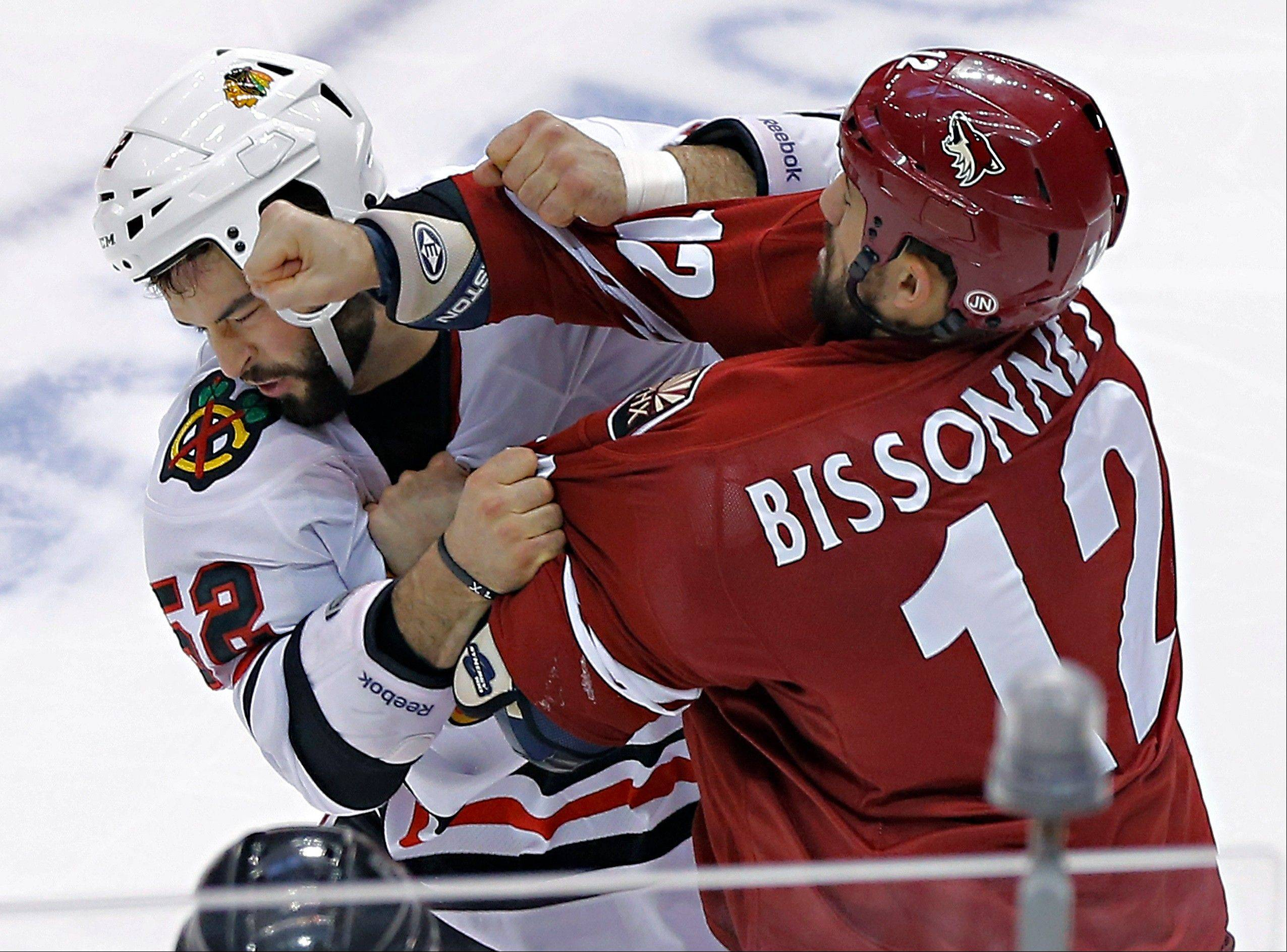 Phoenix Coyotes' Paul Bissonnette (12) and Chicago Blackhawks' Brandon Bollig (52) fight during the second period of an NHL hockey game Sunday in Glendale, Ariz. The Hawks would go on to win 6-4.