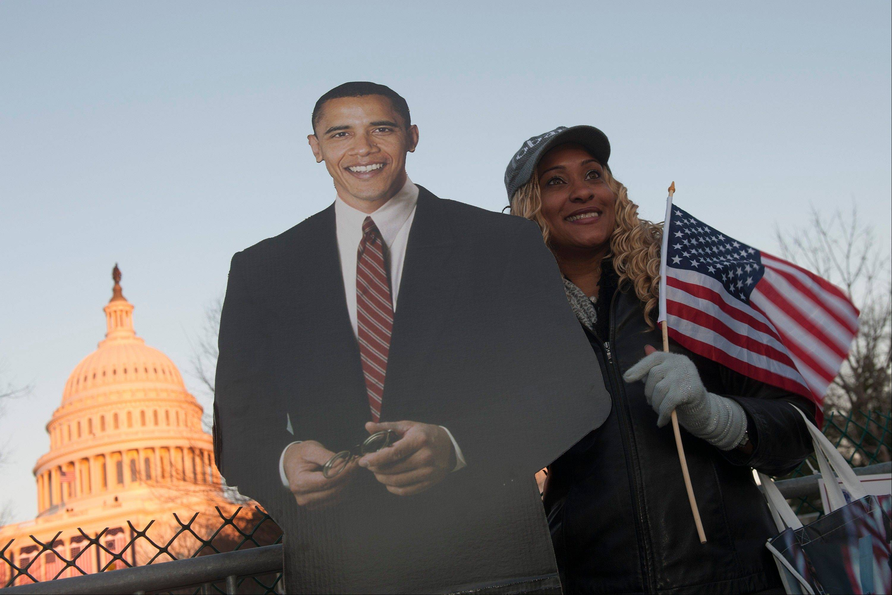 A woman holding a U.S. flag stands for a photograph with a cardboard cutout of President Barack Obama is displayed in front of the Capitol building ahead of the presidential inauguration in Washington, D.C., U.S., on Sunday, Jan. 20, 2013.