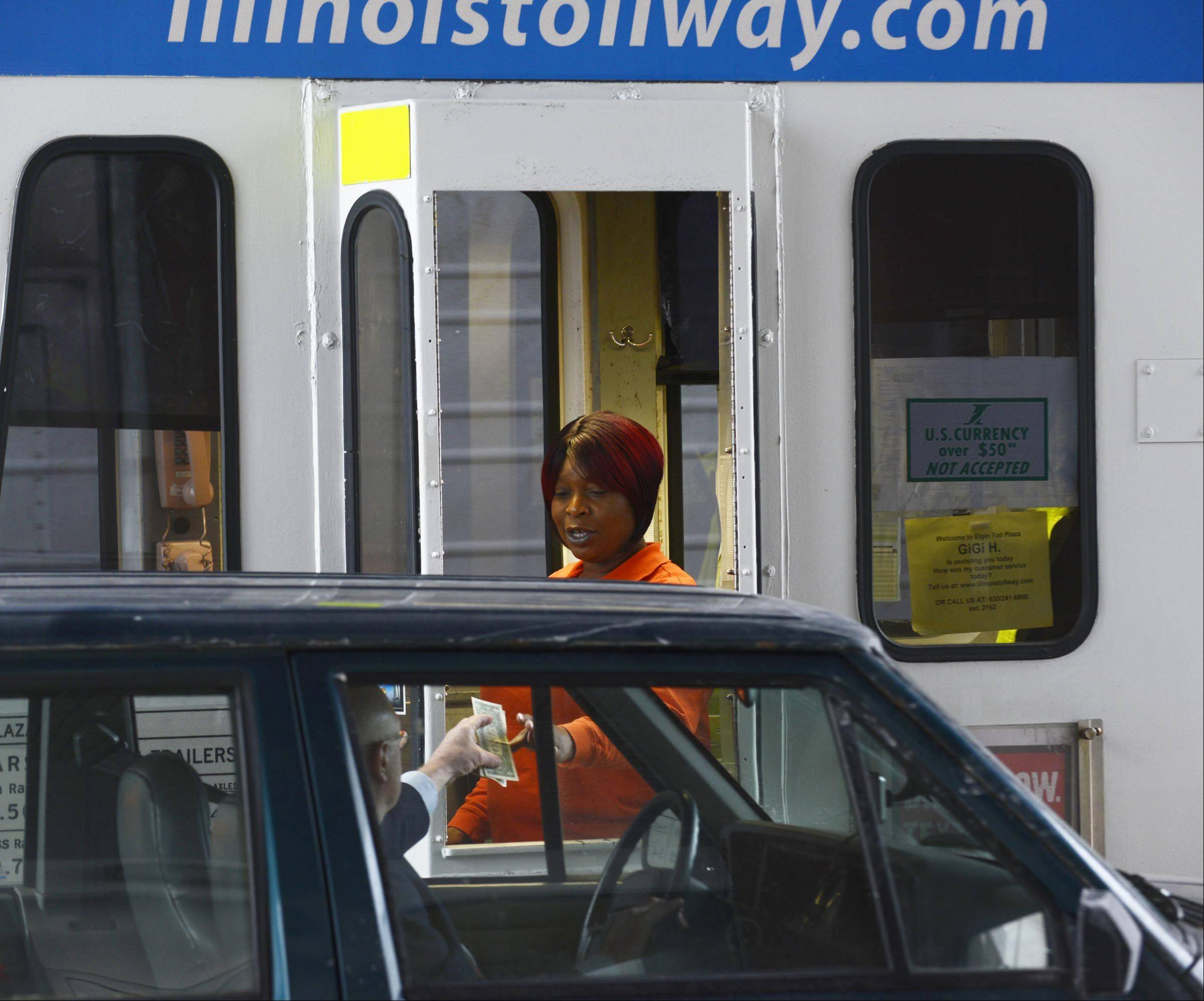 Toll Collector Lagwanda Hudson hands over change to a driver at the Elgin plaza on the Jane Addams Tollway.
