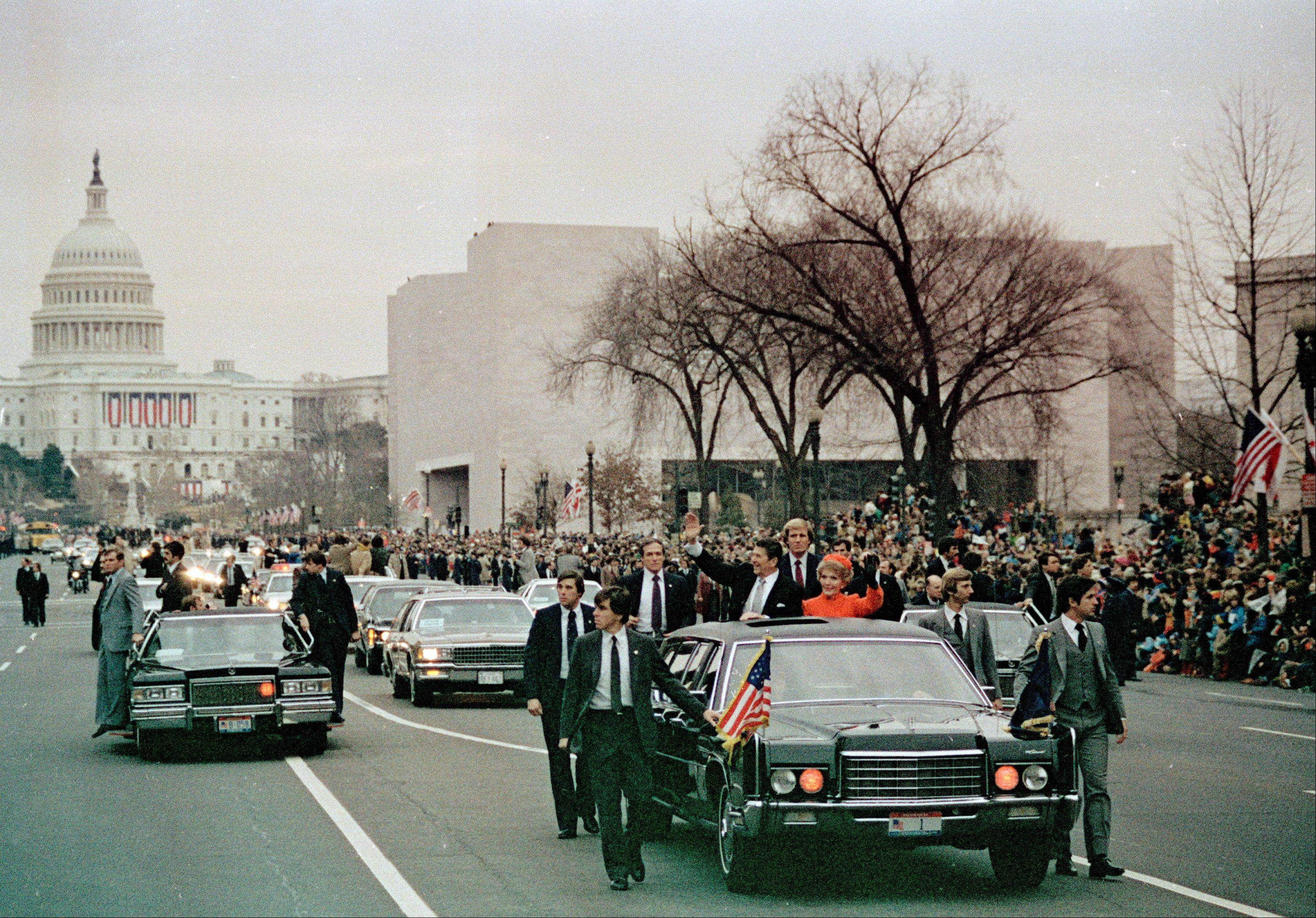 U.S. President Ronald Reagan, left, and first lady Nancy Reagan wave to the crowd from their limousine as they lead the motorcade down Washington's Pennsylvania Avenue on inauguration day, Jan. 20, 1981, following swearing-in ceremony.