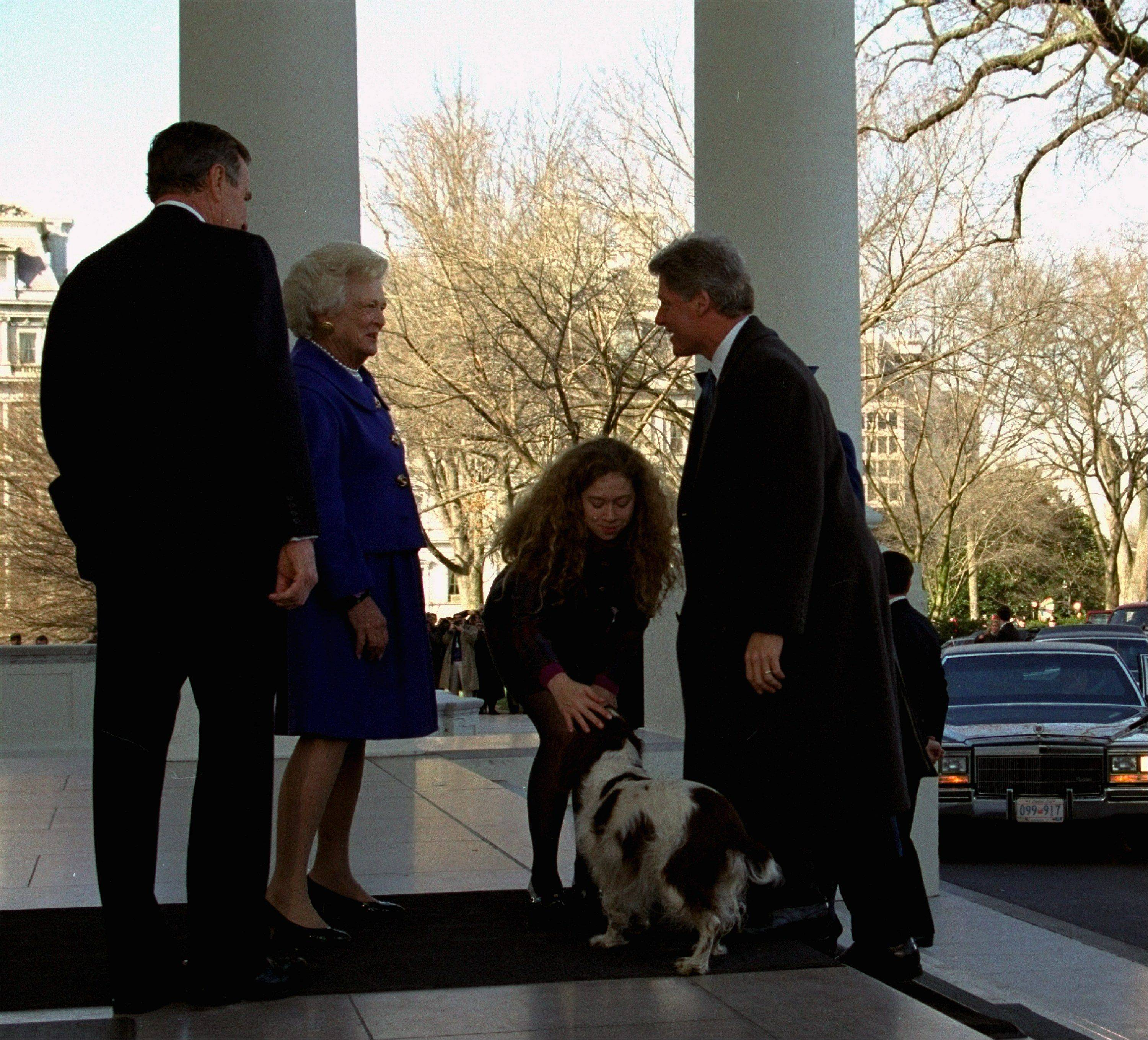 Chelsea Clinton pets outgoing first dog Millie as President Bush, Barbara Bush and President-elect Clinton look on at the White House Wednesday, January 20, 1993. The Clinton family went to the White House to pick up the Bushes, escorting them to Capitol Hill and Clinton's presidential swearing in ceremony.