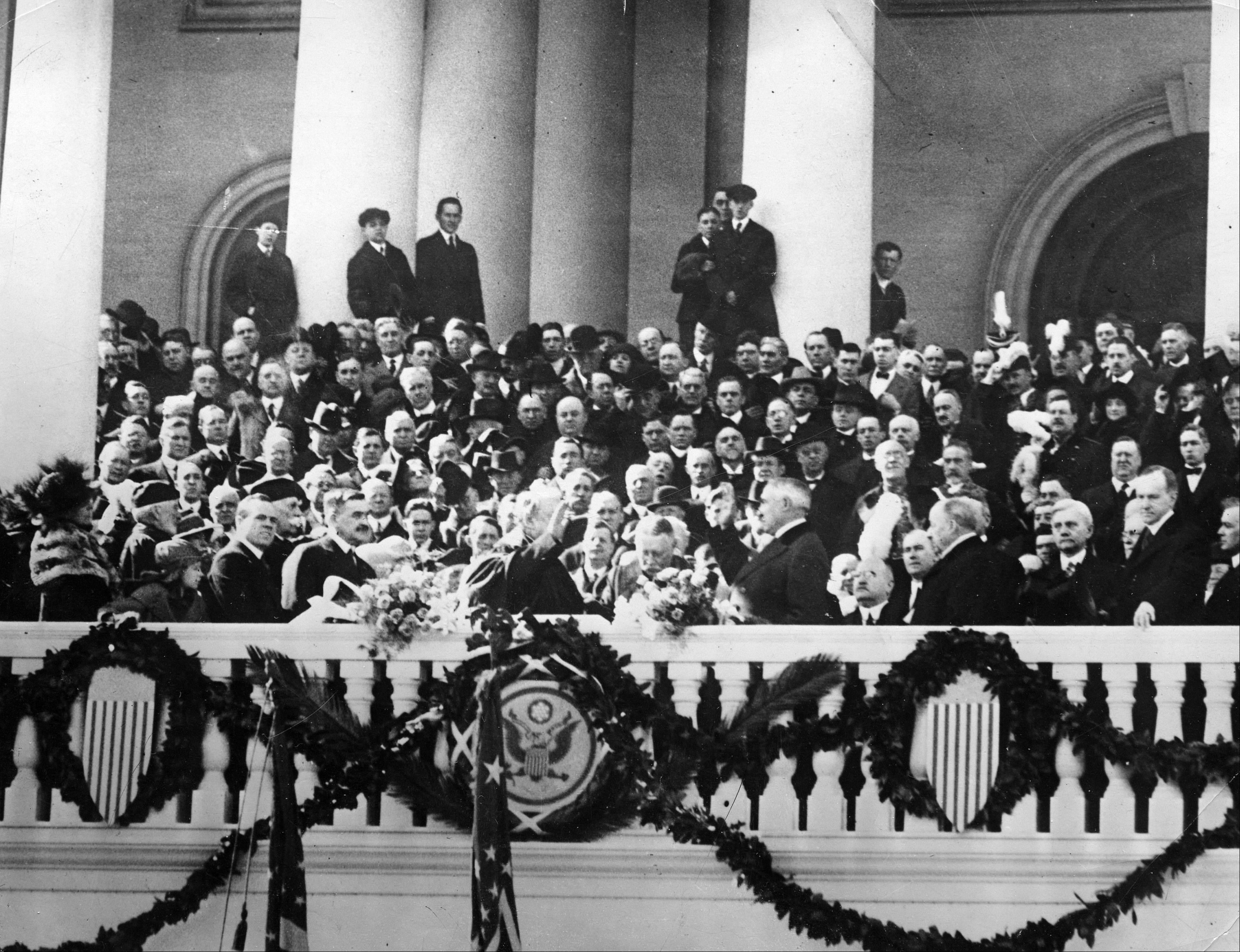 Warren G. Harding, center right, takes the oath of office administered by Chief Justice Edward D. White on the East Portico of the Capitol building in Washington, D.C., March 4, 1921. Harding is sworn in as the 29th president of the United States.